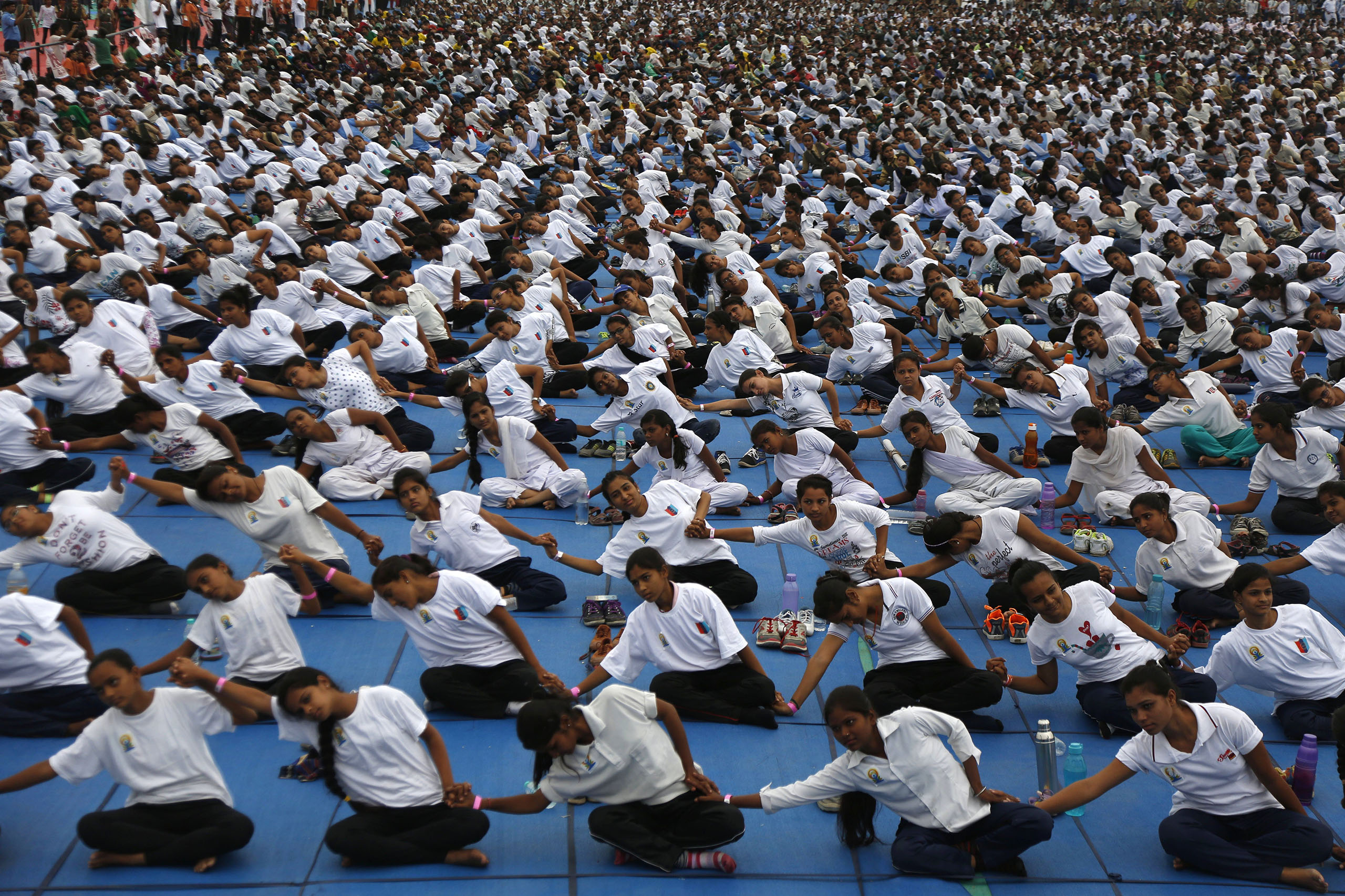 Indians holds hands as they attempt to create a record for the longest human yoga chain with more than 8000 participants at an event to celebrate International Yoga Day in Ahmadabad, India, June 21, 2016.