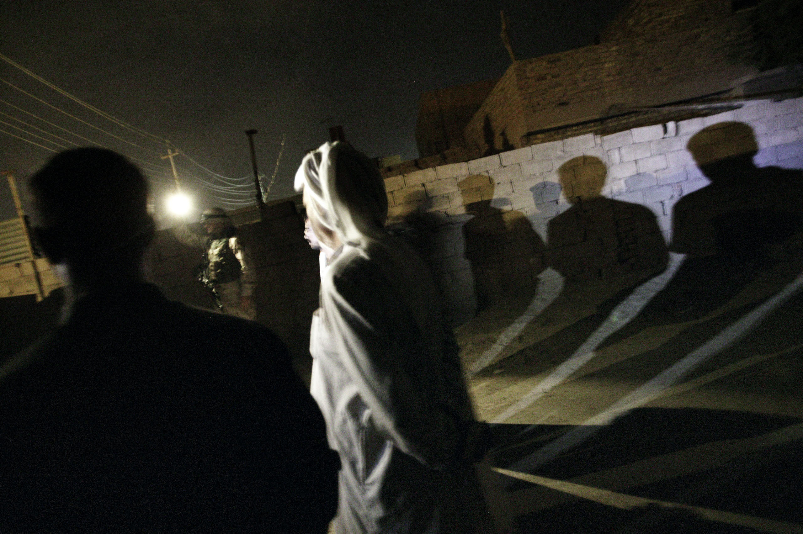 U.S. soldiers from the 2-12 Cavalry Regiment detain men during an early morning raid in the restive Abu Ghraib area of Baghdad, Oct. 20, 2004.