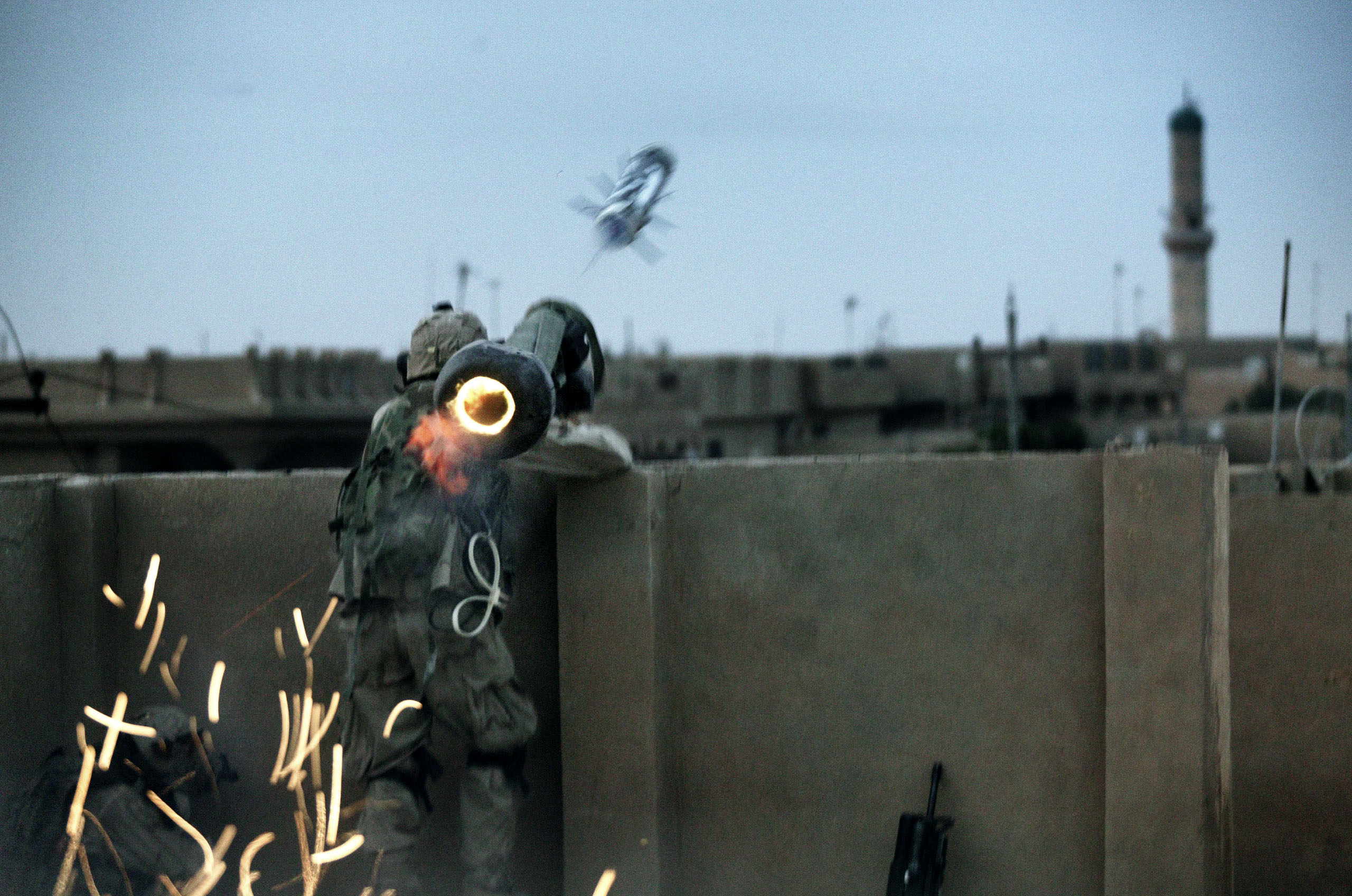 Dawn breaks in Fallujah, Iraq, as the U.S. military launched a massive offensive to retake the city from Sunni insurgents. A soldier with the Army Task Force 2-2's Alpha Company, 3rd Platoon, fires a rocket at insurgent positions from a makeshift rooftop, Nov, 9, 2004.