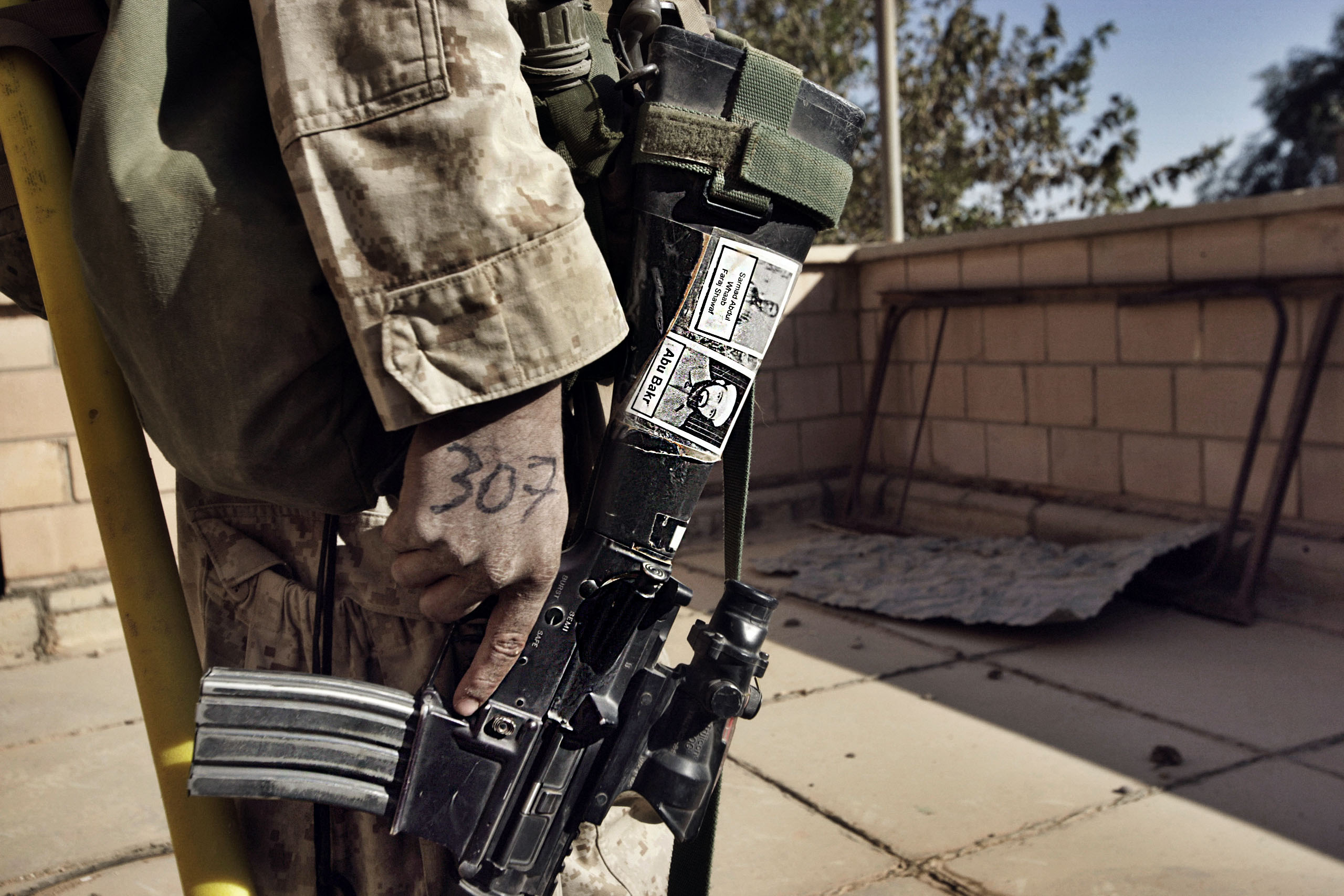 A Marine from Fox Co. 2nd Battalion 1st Marines holds his M-16 rifle with  pictures of suspected insurgents during the first day of Operation Steel Curtain, an effort to root out foreign fighters and extremists, Nov. 5, 2005.