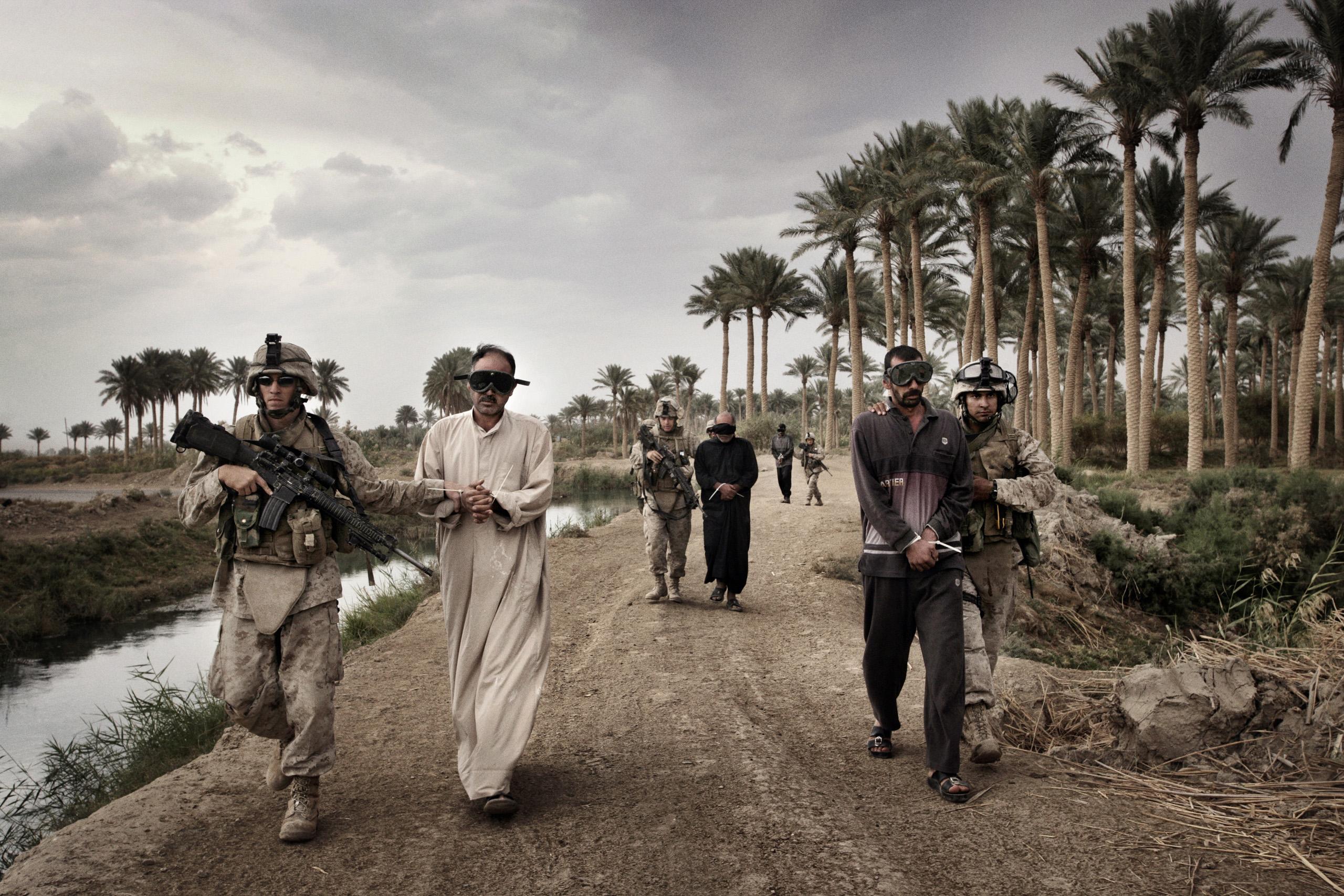Marines escort suspected insurgents, including Ali Muhammad Said, accused of leading a mortar team in attacking Camp Delta outside al-Karmah, Fallujah, Iraq, Oct. 29, 2005.