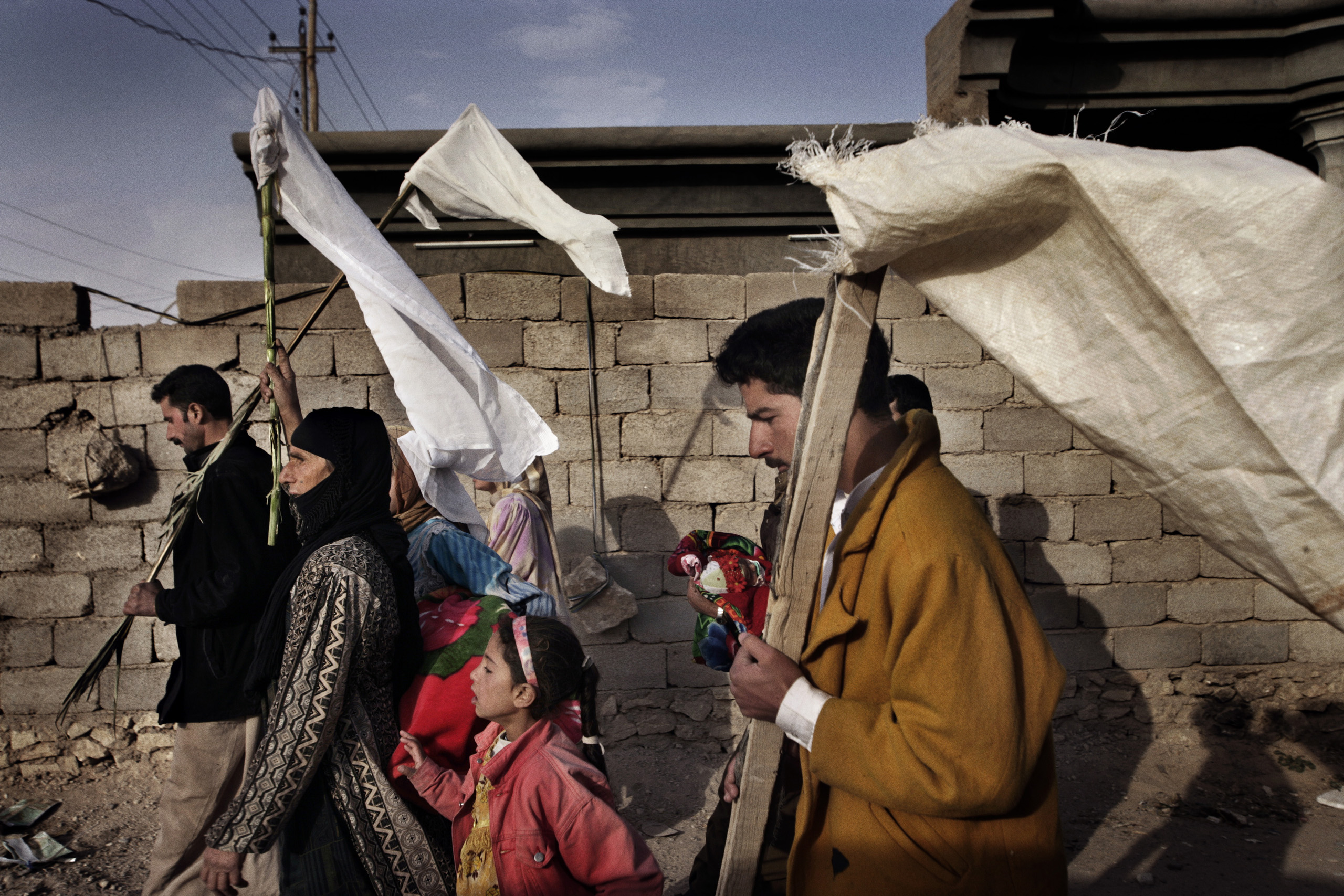 Iraqi civilians wave white flags for protection while fleeing the city of Husaybah during Operation Steel Curtain, a joint American-Iraqi offensive to stop the flow of insurgents crossing the Iraqi-Syrian border, Nov. 7, 2005.