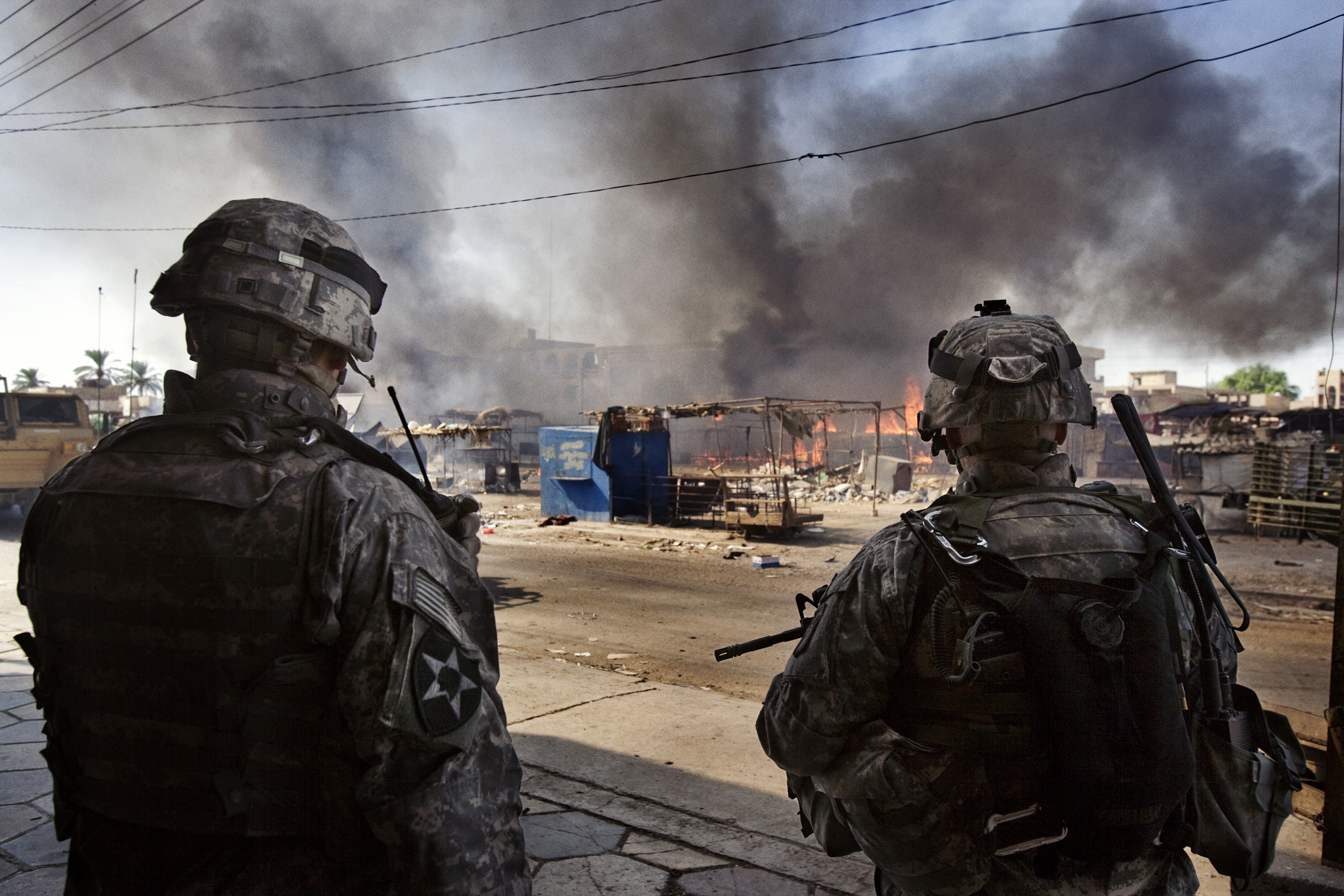 US soldiers of  the 2nd Battalion, 506th INF Regiment 101 Airborne DIV attached to 4th Brigade Combat Team 4th INF DIV  watch a fire  at a market in Al Dora, a neighborhood controlled by Sunni extremists, Baghdad, Iraq, Sept. 28, 2006.