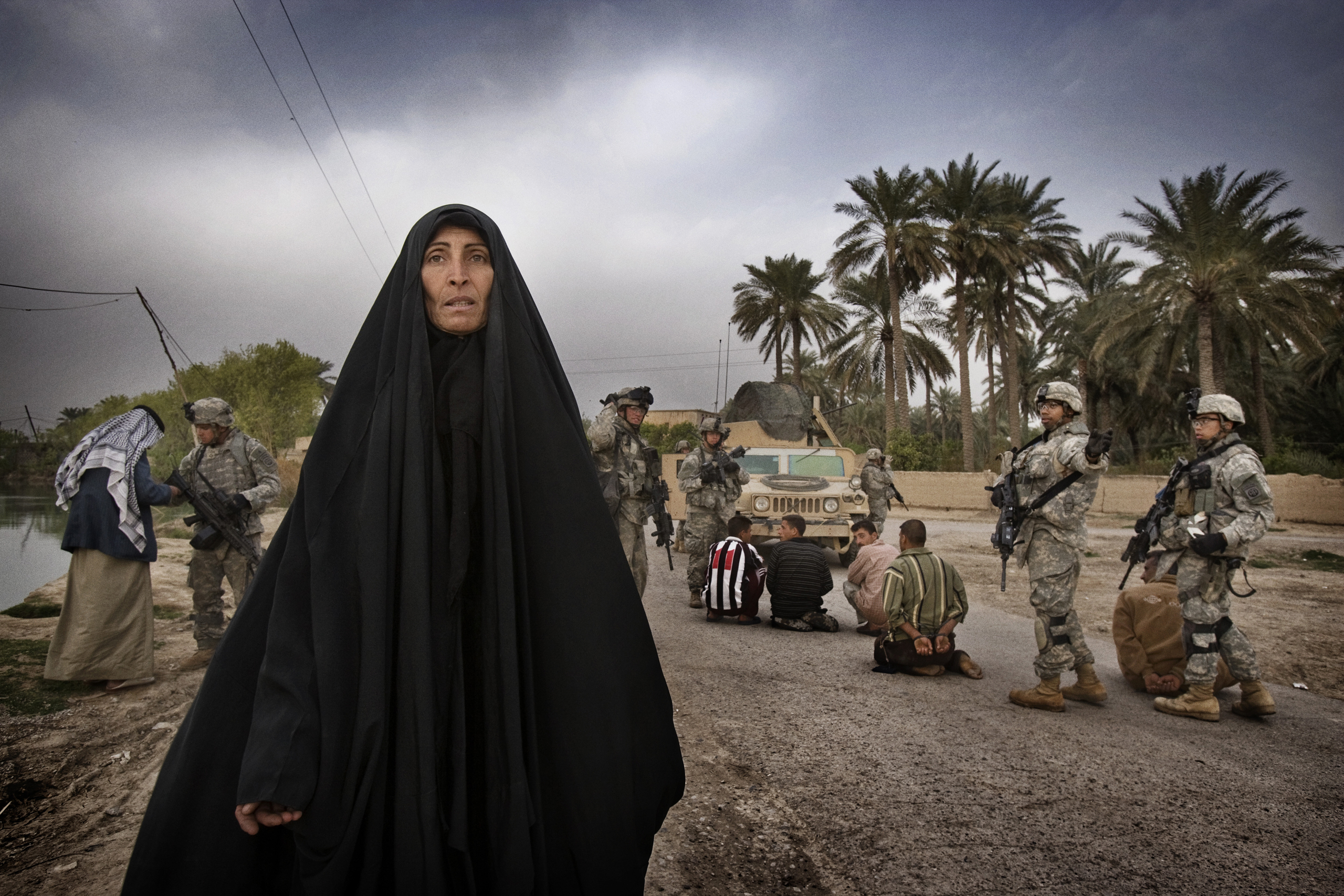 U.S. soldiers from A Troop 5th Squadron 73rd Cavalry detain suspected insurgent sympathizers after killing a militant caught laying a roadside bomb on the outskirts of Baquba. Women from the village begged for the release of the men as U.S. soldiers led them away, Zurah, Iraq, March 15, 2007.