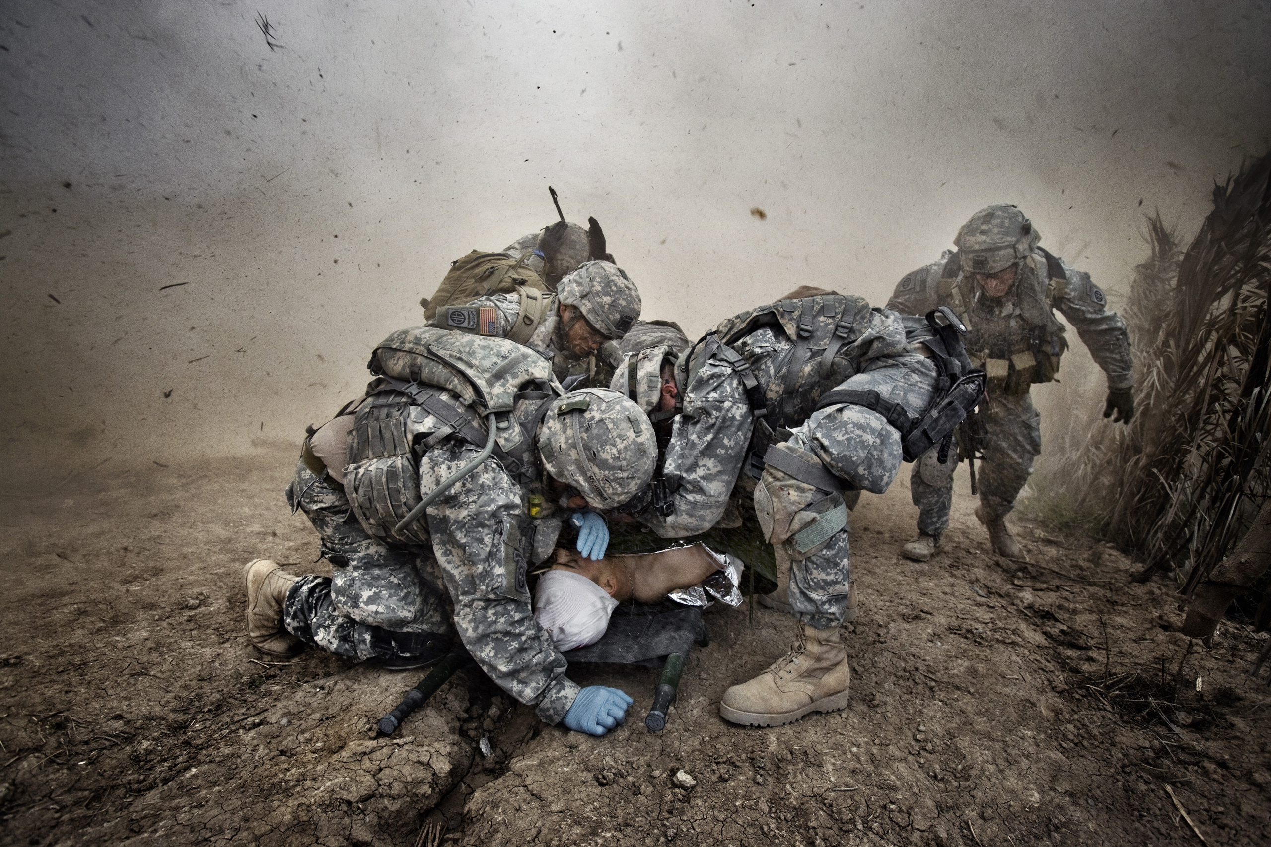 U.S. soldiers shield a wounded comrade from debris kicked up by a rescue helicopter descending on Qubah, Iraq, March 24, 2007. Fighting between U.S. forces and insurgents erupted in the village at dawn, when U.S. troops stormed the city and began house-to-house searches for guerrilla fighters. Two U.S. troops were wounded in the clashes. Sixteen suspected insurgents were killed.