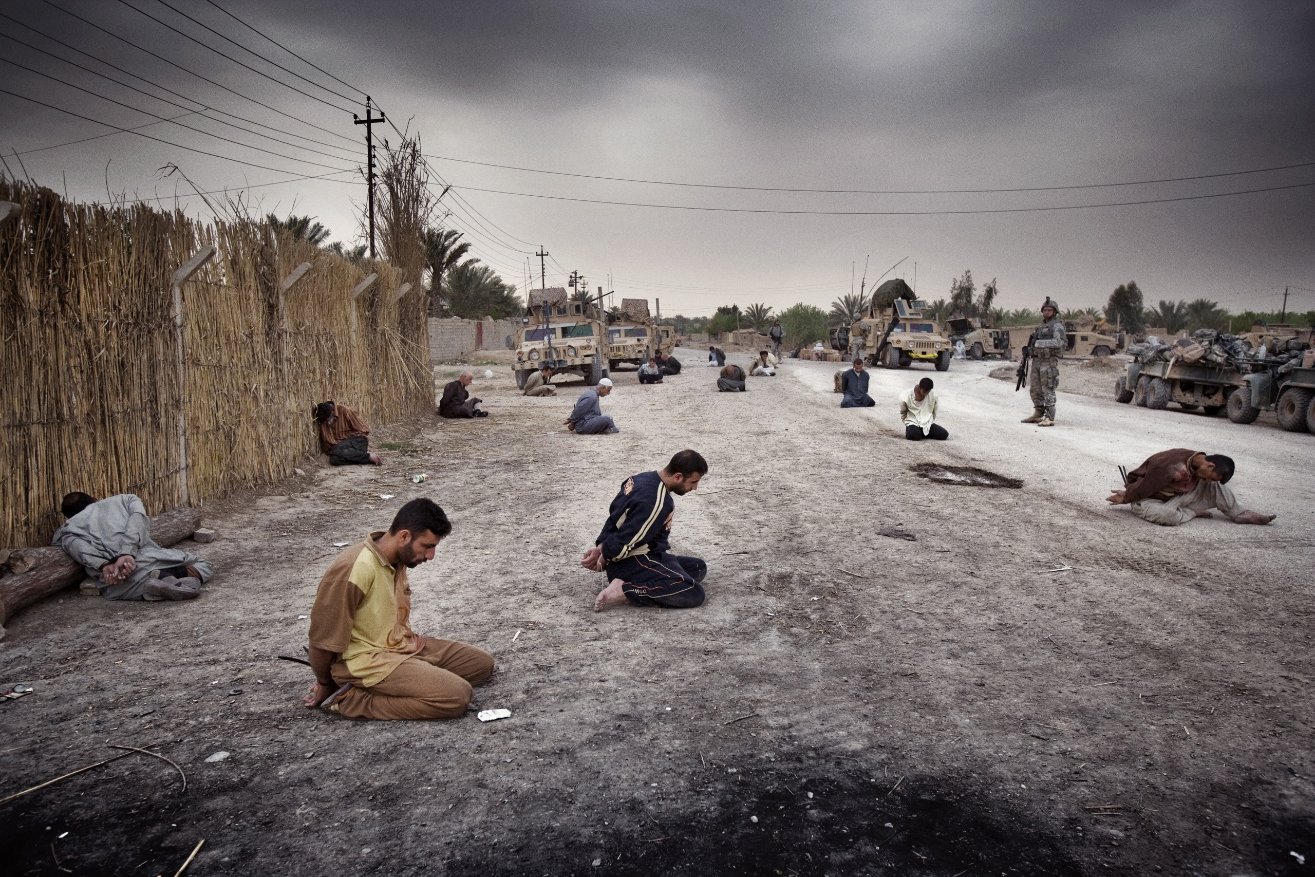 Men arrested by U.S. forces sit bound in the street after a roadside bomb attack in Qubah, Iraq, that left four Americans and one Iraqi boy dead, March 25, 2007.