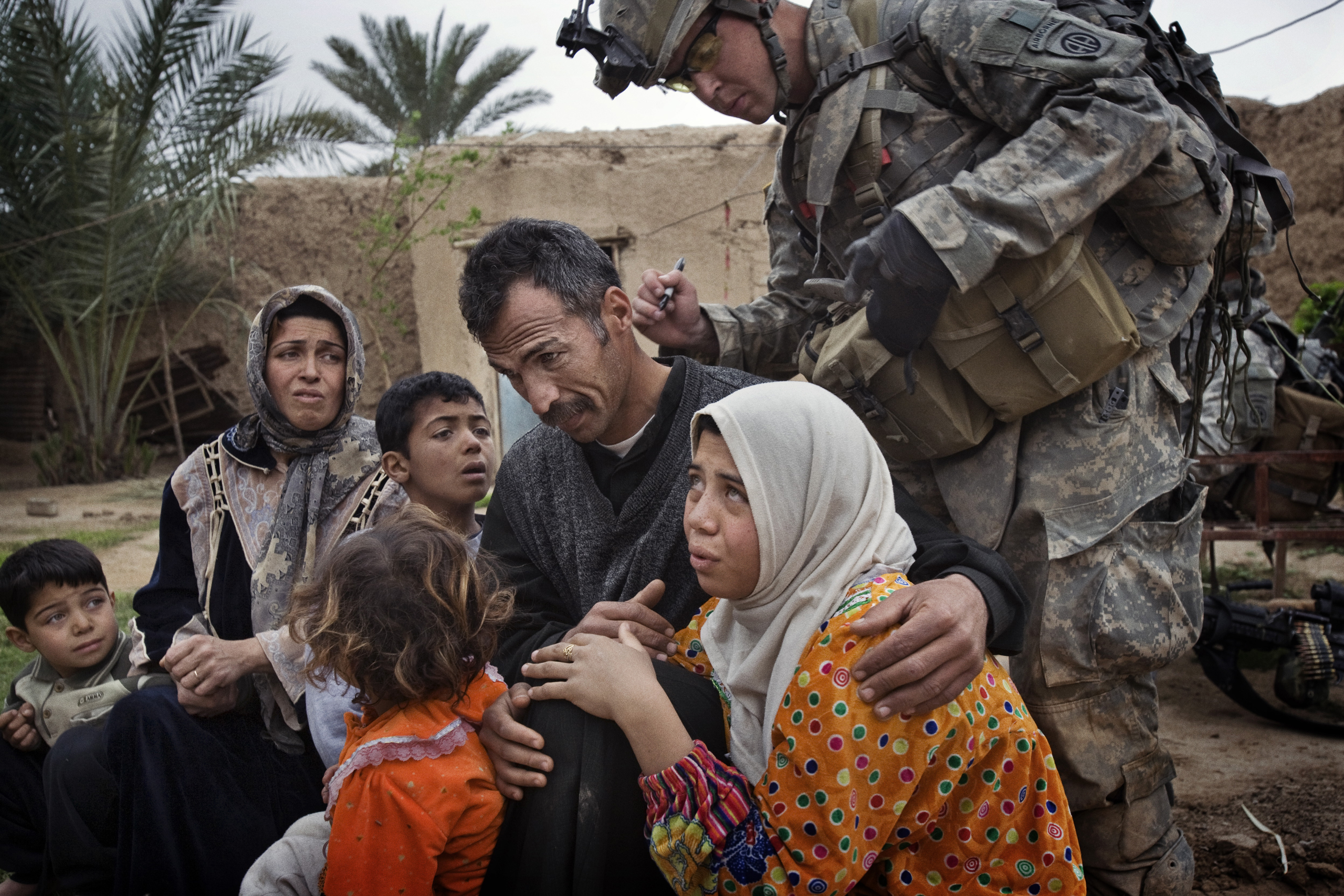A  U.S. soldier marks the neck of a man with identifying numbers. The numbering system allowed U.S. troops to tell whether anyone was moving about the village, despite a lockdown, Qubah, Iraq, March 24, 2007.