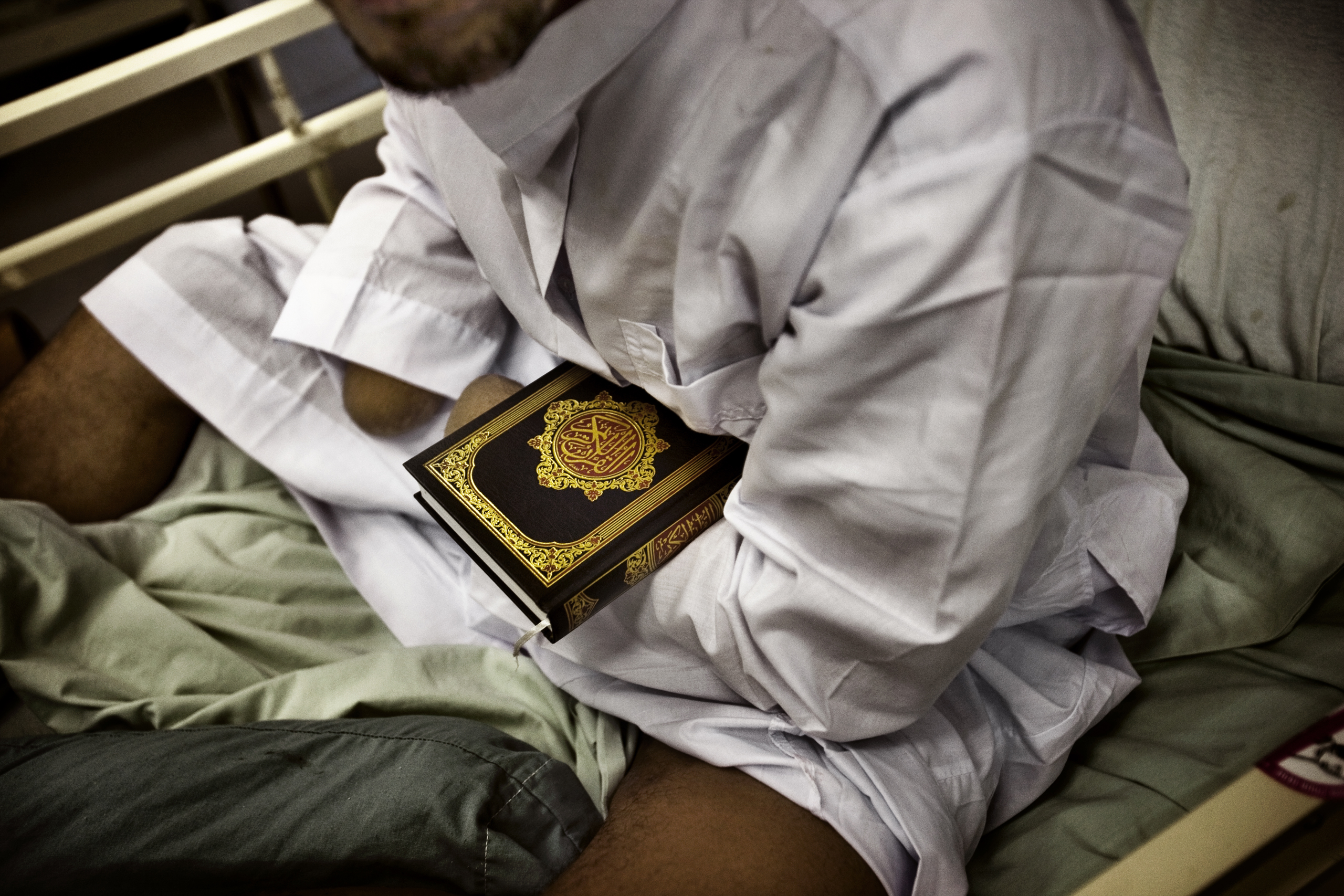 A detainee patient, who nurses say likely lost his hands while handling explosives, holds a Quran at the hospital at Camp Cropper, a U.S. military detention facility in Baghdad, July 26, 2008.