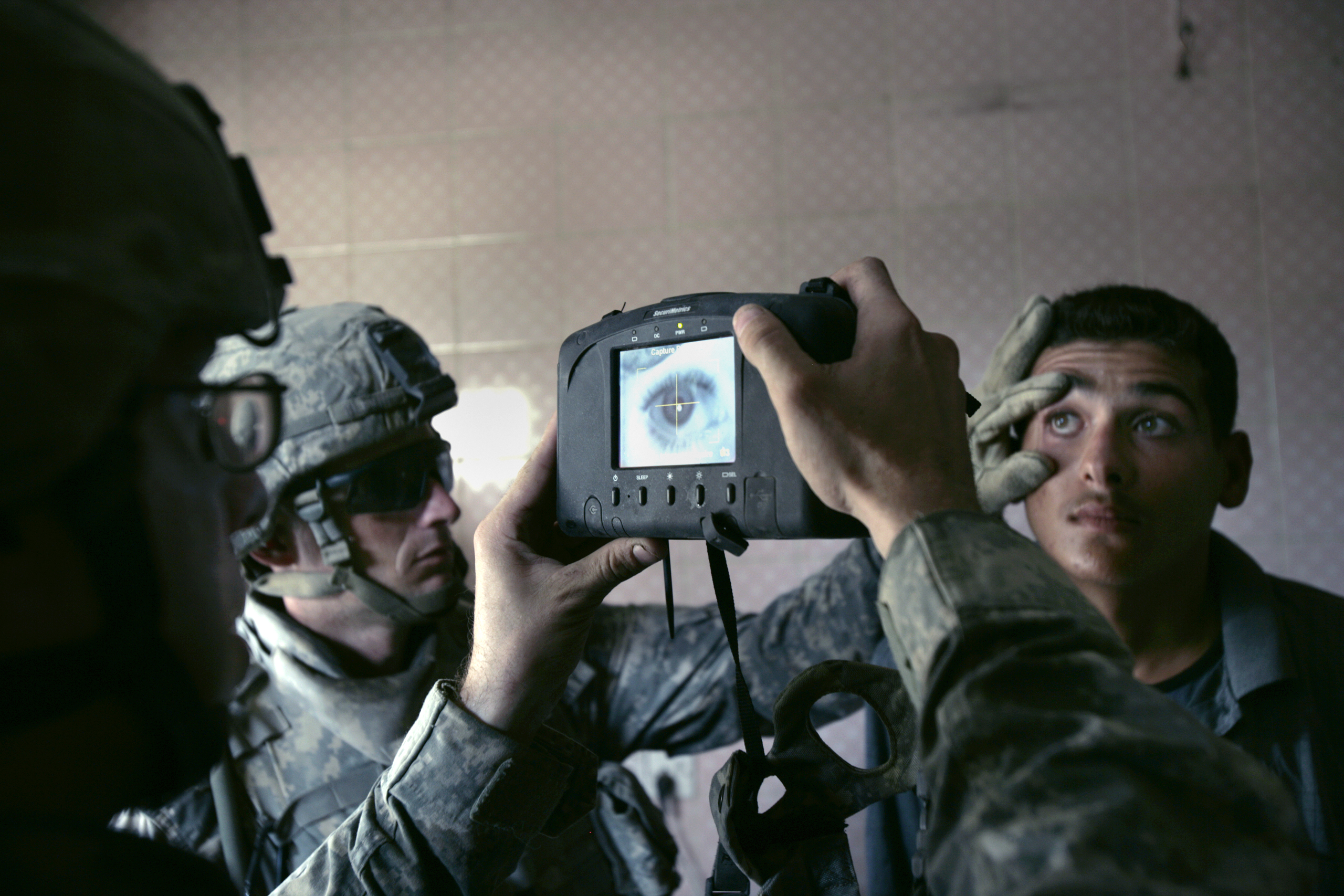 A U.S. Army soldier with 1st Battalion, 5th Cavalry Regiment, 2nd Brigade, 1st Cavalry Division scans an Iraqi man's eye during a census operation in the Amariyah neighborhood of west Baghdad, Aug. 5, 2007. The  American soldiers try to take the name, address and  biometrics  of each Iraqi man they meet during searching the houses.
