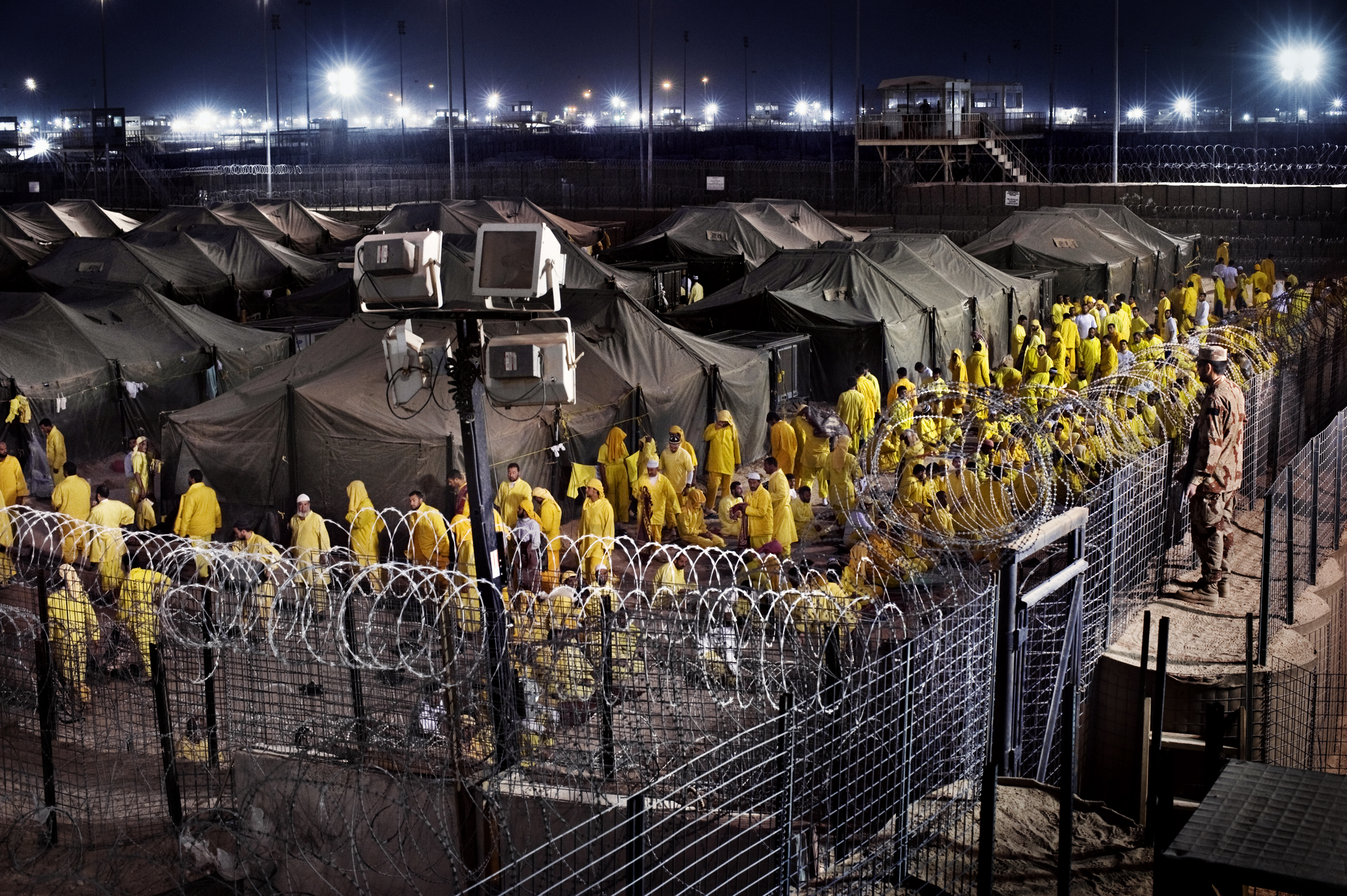 Detainees walk after prayer at Camp Bucca, a U.S. military detention center, March 16, 2009. At its peak, the prison located 340 miles southeast of Baghdad held 26,000 detainees.