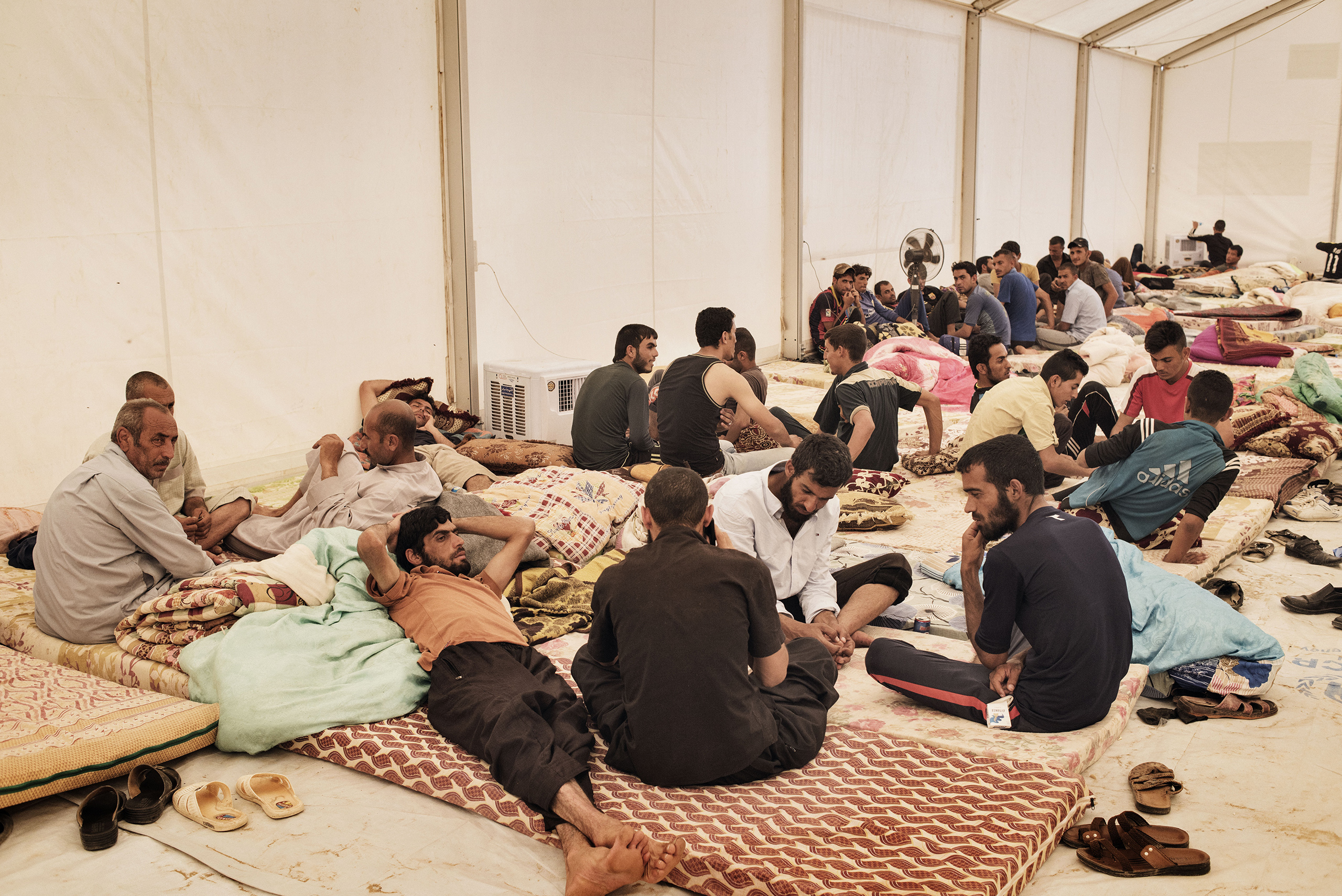 Men sit and lay down in a tent at a camp for displaced families near the Iraqi town of Makhmour, in northern Iraq, May 13, 2016.