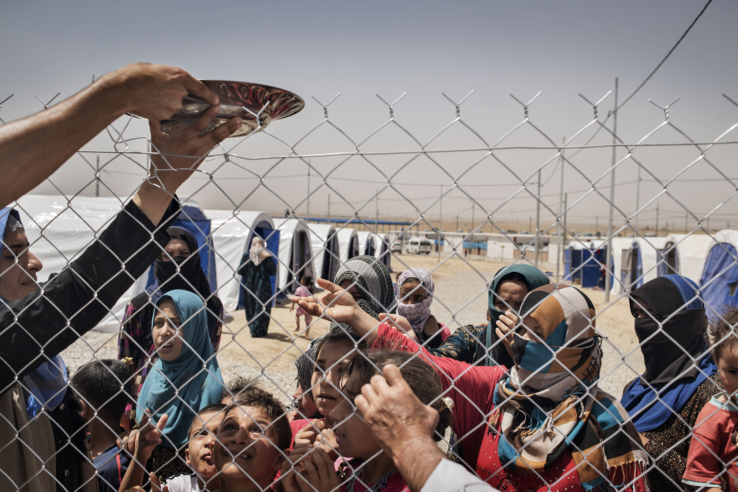 Displaced people stand in front of a fence in a camp near the Iraqi town of Makhmour, in northern Iraq, May 13, 2016. The United Nations said in April that as many as 30,000 people could be forced to flee instability in the Makhmour area, as the Iraqi military pursues an offensive against Islamic State militants in the district.