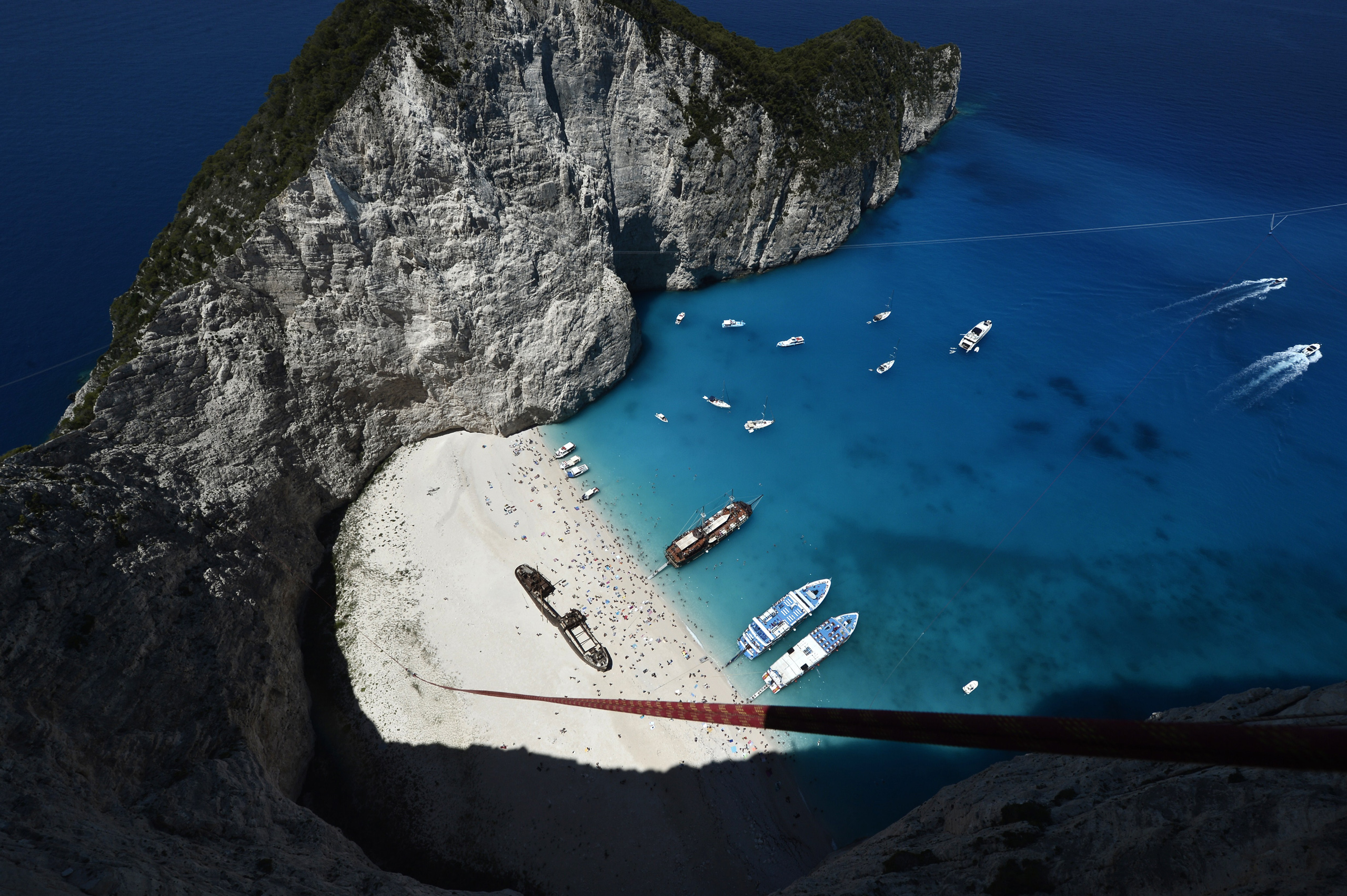 Rugged rocks overlooking the azure waters of Navagio beach on the popular tourist island of Zakynthos, Greece on June 23, 2014.