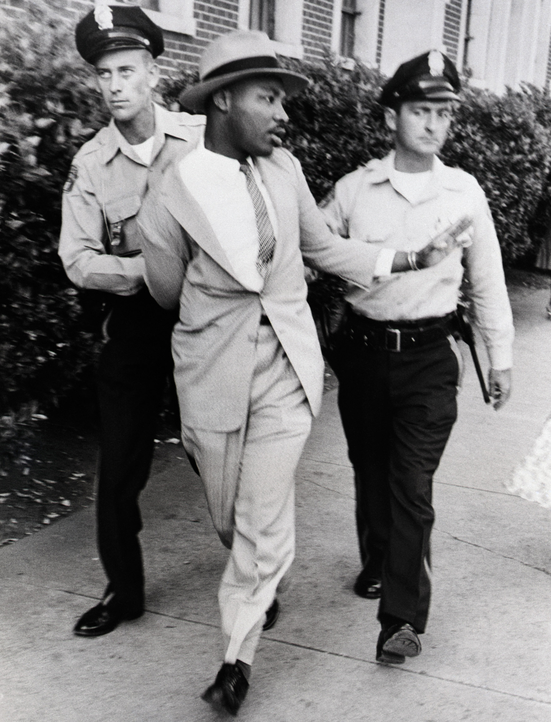 Police officers O.M. Strickland and J.V. Johnson apply force in arresting the Reverend Martin Luther King for loitering near a courtroom where one of his integration lieutenants was on the stand. King charged he was beaten and choked by the arresting officers. Police denied the charges. 1958.