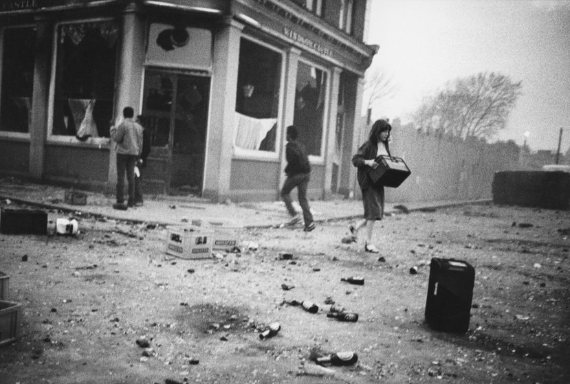 YOUNG LOCALS RELIEVING THE BURNED OUT LOCAL PUB 'THE WINDOW CASTLE' OF ITS CONTENTS ON THE FIRST NIGHT OF THE RIOTS, BRIXTON, APRIL, 1981