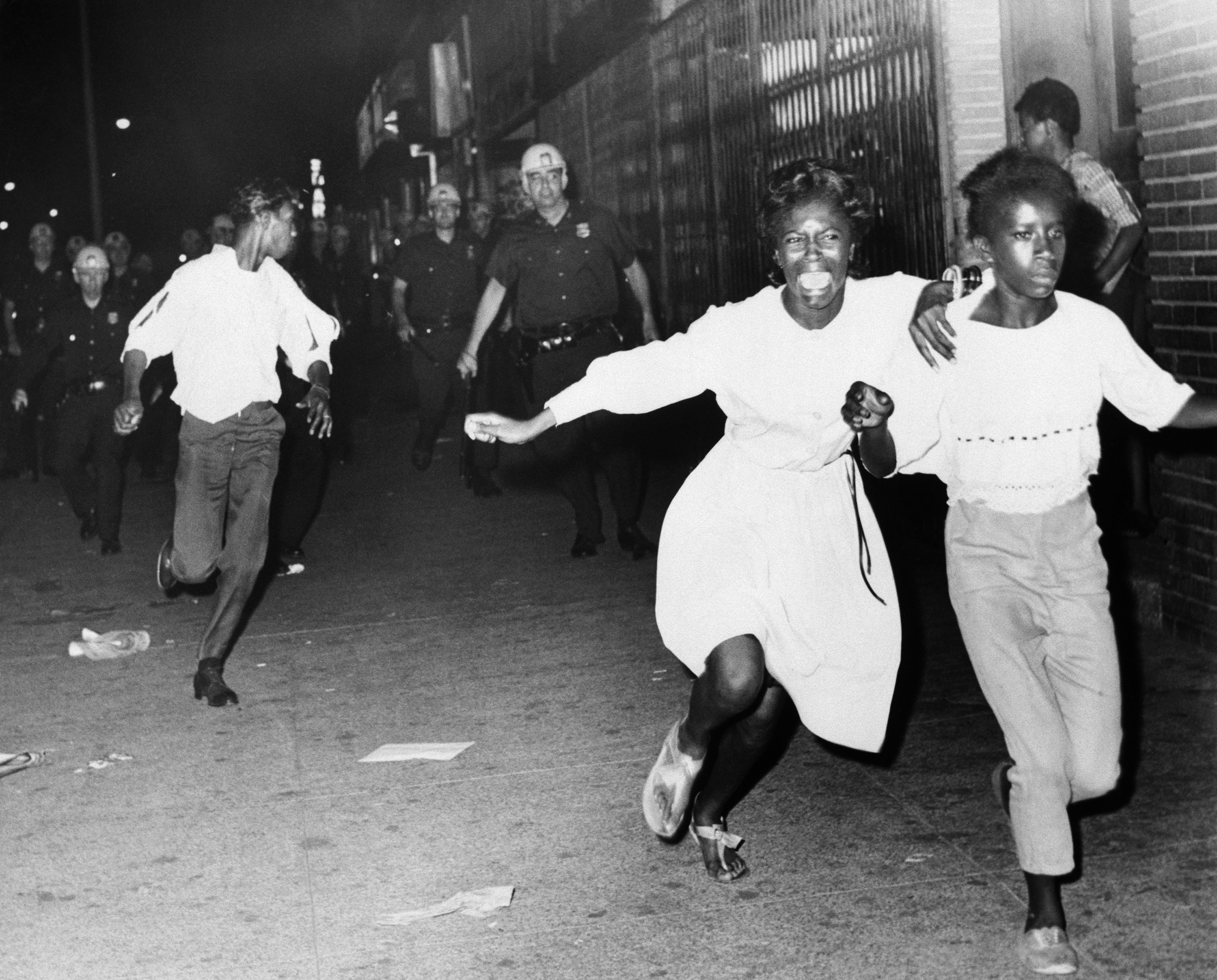 Two terrified African American girls flee police officers during a race riot in the Bedford-Stuyvesant neighborhood of Brooklyn. 1964.