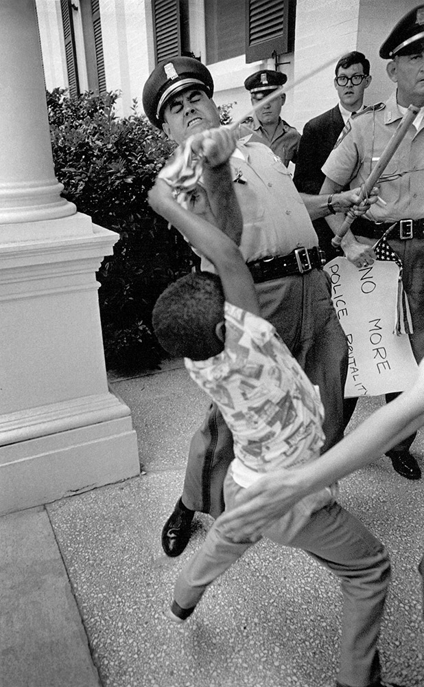 Mississippi Highway patrolmen  arrests Anthony Quin, 5, son of Mrs. Aylene Quin  during voting rights protest. When Quinn refused to give up small American flag, patrolman went berserk, wrenched it out of his hands.  June 17, 1965, Jackson, Mississippi.