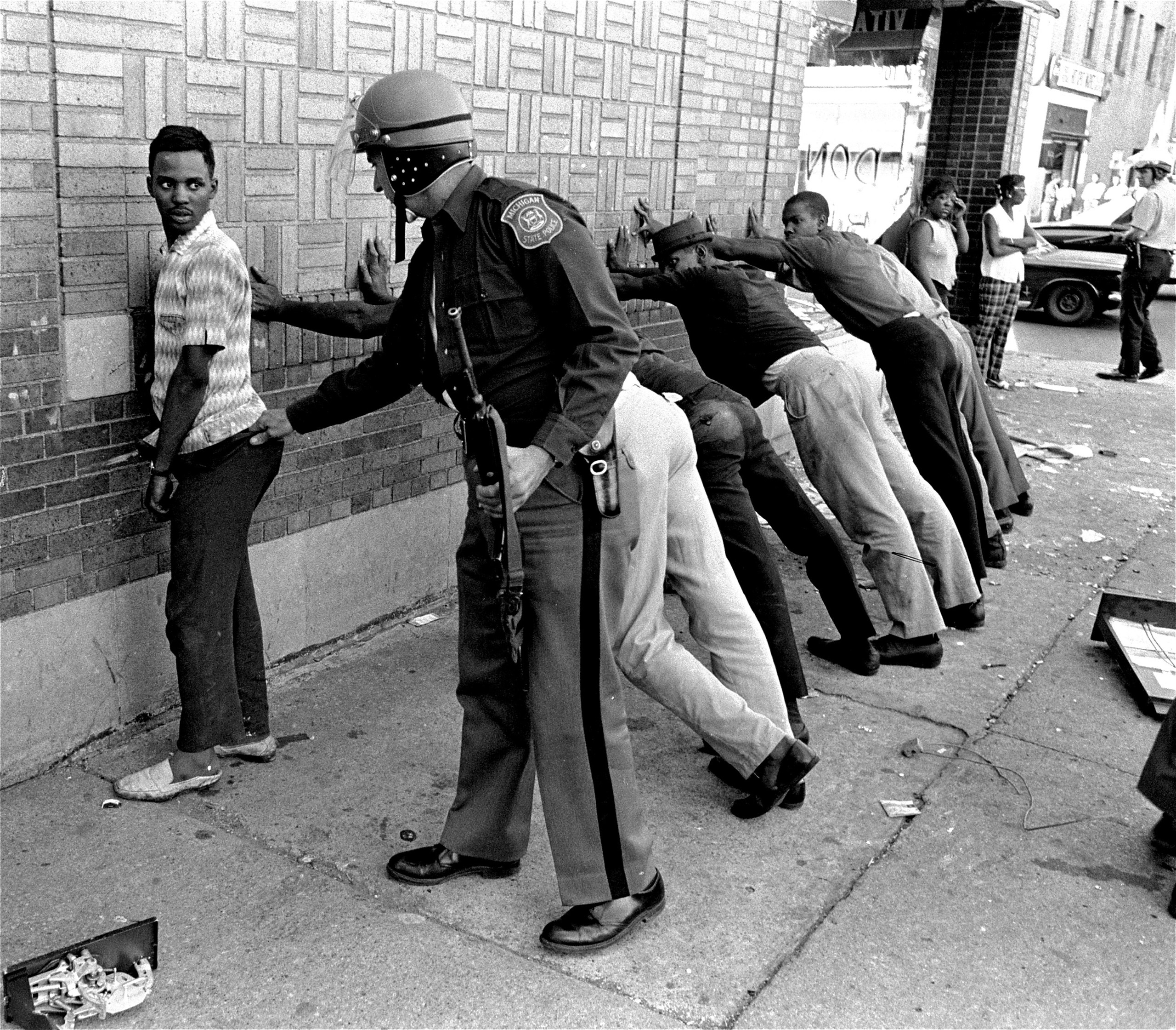 A Michigan State policeman searches a youth on Detroit's 12th Street, July 24, 1967, where looting was still in progress.