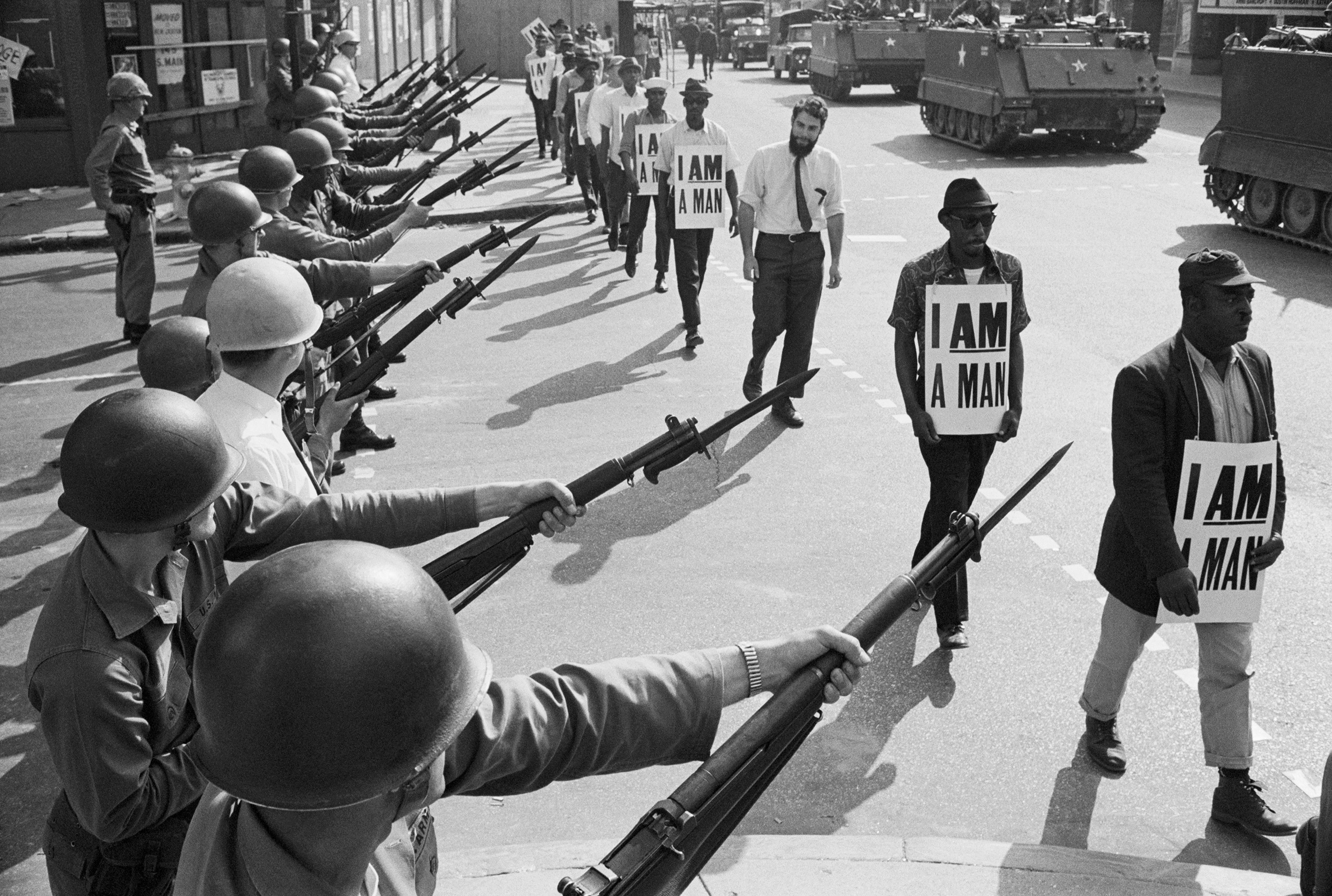 U.S. National Guard troops block off Beale Street as Civil Rights marchers wearing placards reading,  I AM A MAN  pass by on March 29, 1968. It was the third consecutive march held by the group in as many days. Rev. Martin Luther King, Jr., who had left town after the first march, would soon return and be assassinated.