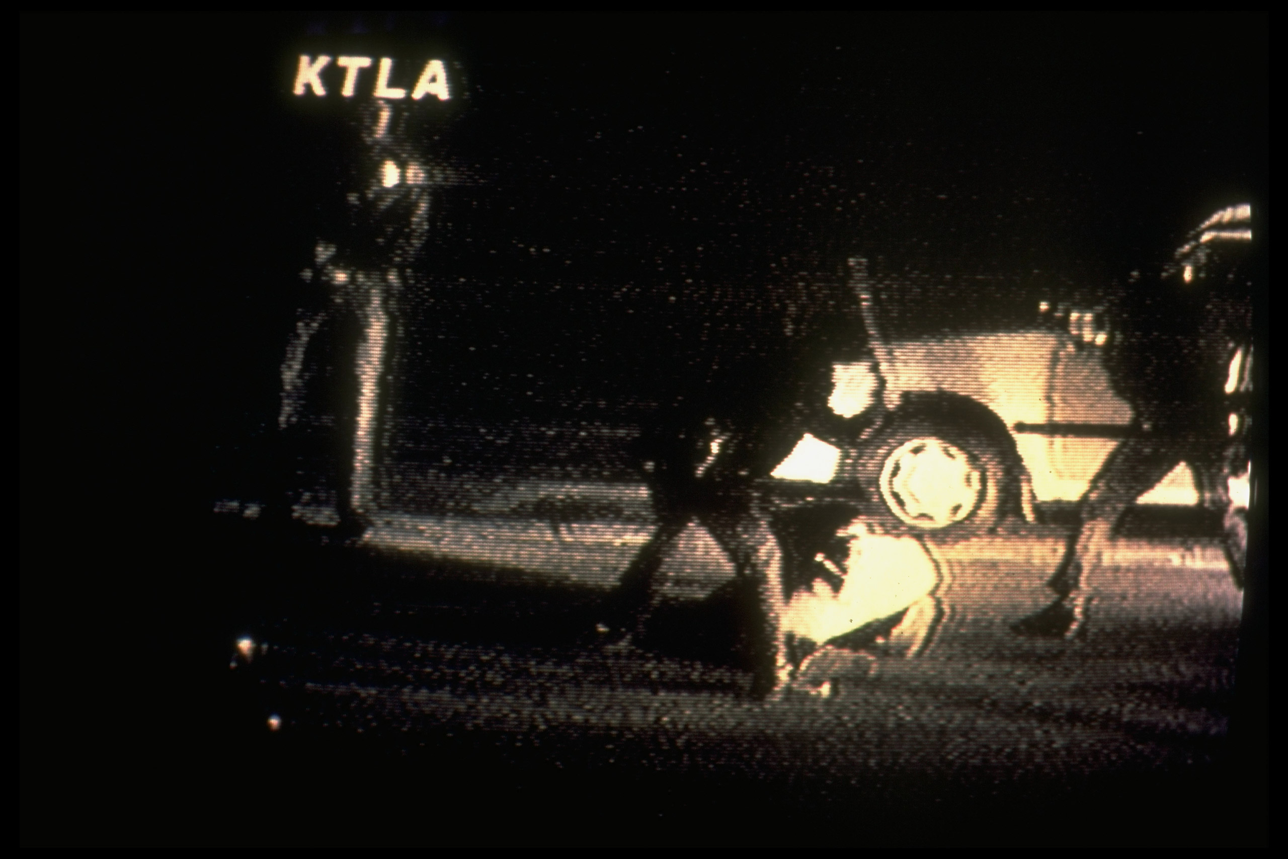 Video image of LA cops beating black motorist Rodney King as he lies on ground; taken by camcorder enthusiast George Holliday fr. window overlooking street. 1991.