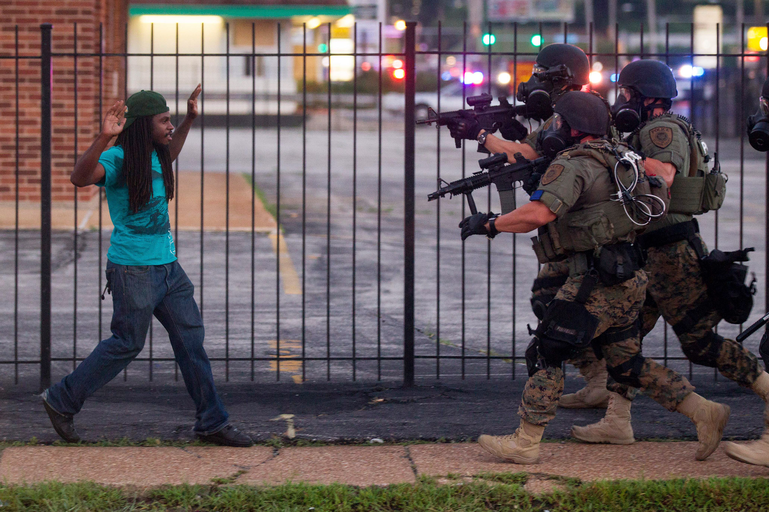 Heavily armed and equipped police confront, and eventually detain, a man during protests two days after the fatal shooting of Michael Brown by a police officer, in Ferguson, Mo., Aug. 11, 2014.