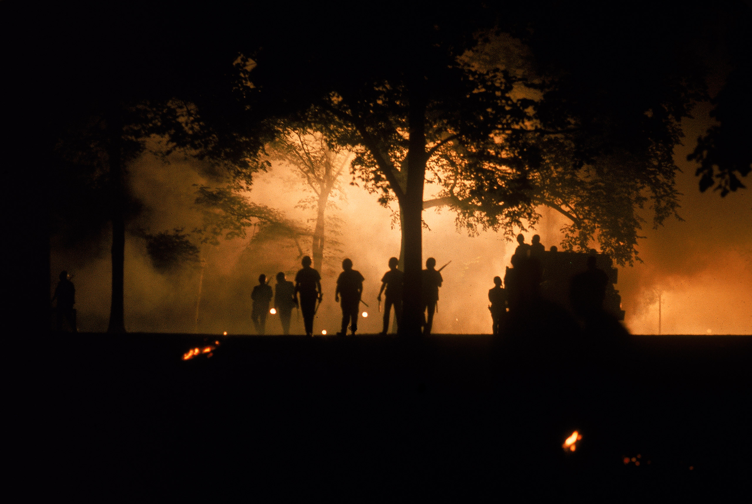 Caption from TIME. Police wearing masks advance through tear gas clouds in Chicago's Lincoln Park.