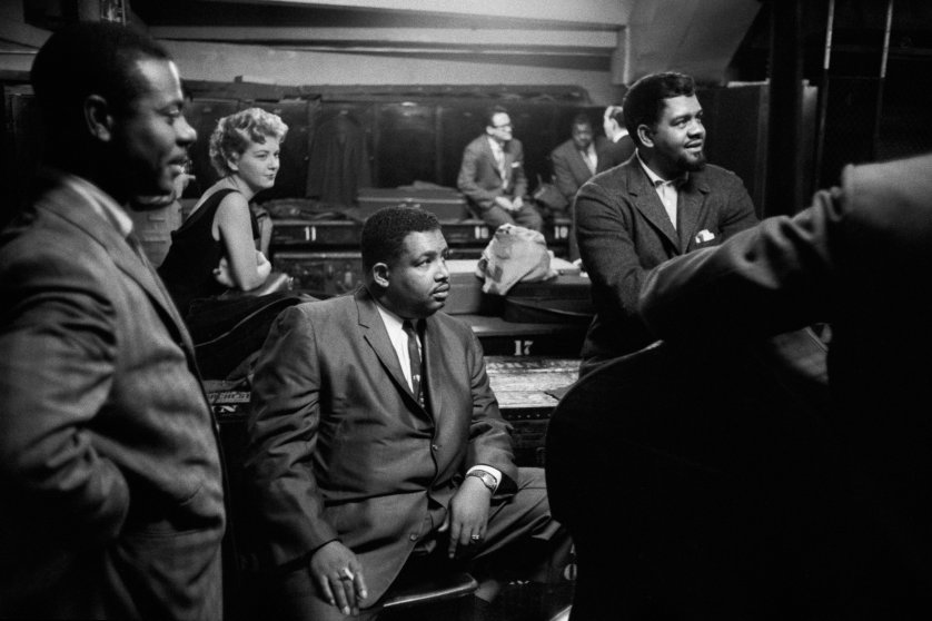 "Armando Peraza, Helen Merrill, ""Cannonball"" Adderley, Al McKibbon, with Toots Thielmans and Oscar Peterson reflected in the mirror, backstage at Orchestra Hall, Chicago, 1957."