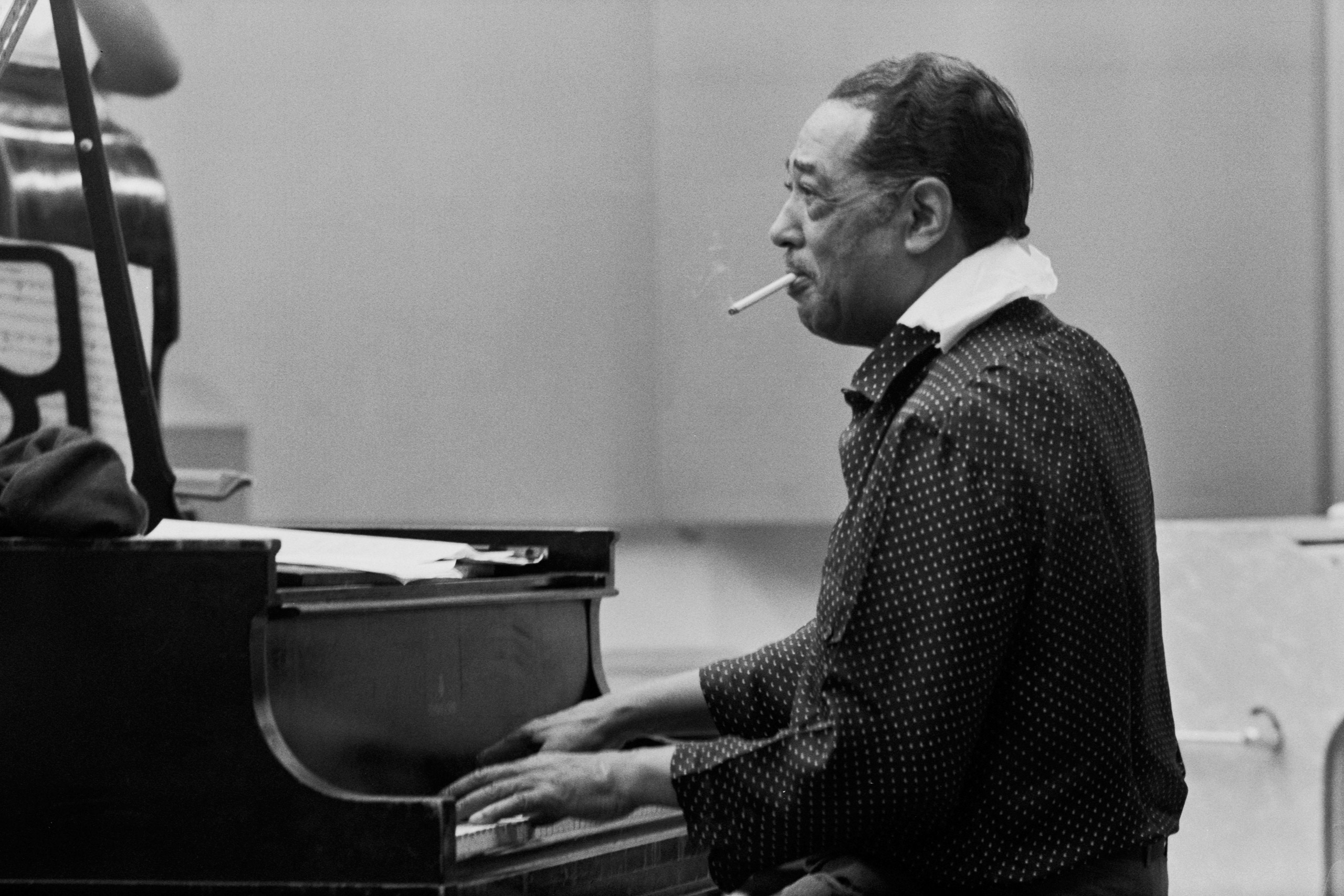 American composer, pianist and bandleader of jazz orchestras, Edward Kennedy  Duke  Ellington, playing piano while smoking a cigarette during a recording session, Chicago,1966.