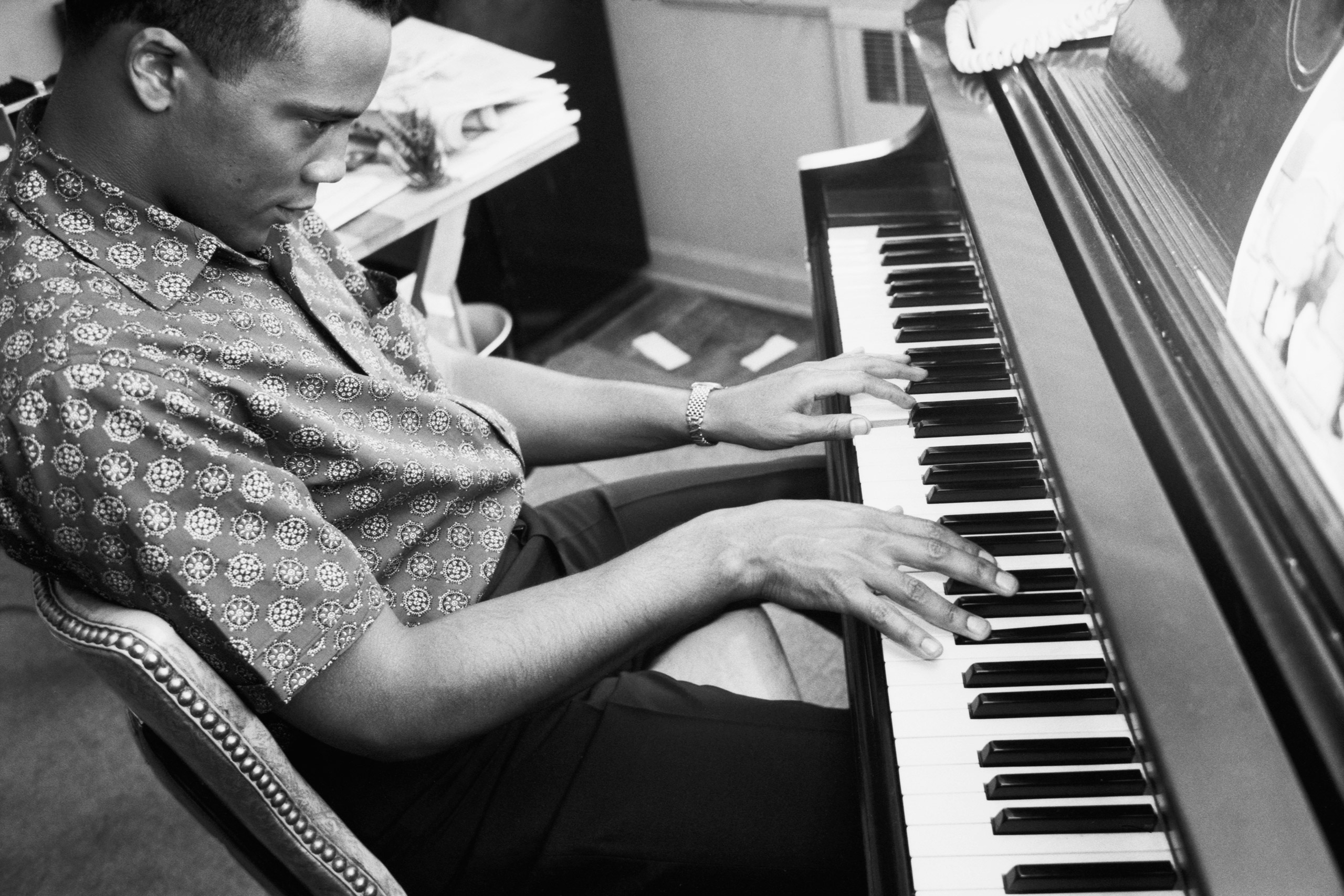 American record producer, conductor, arranger, composer and musician Quincy Jones playing piano at his home.