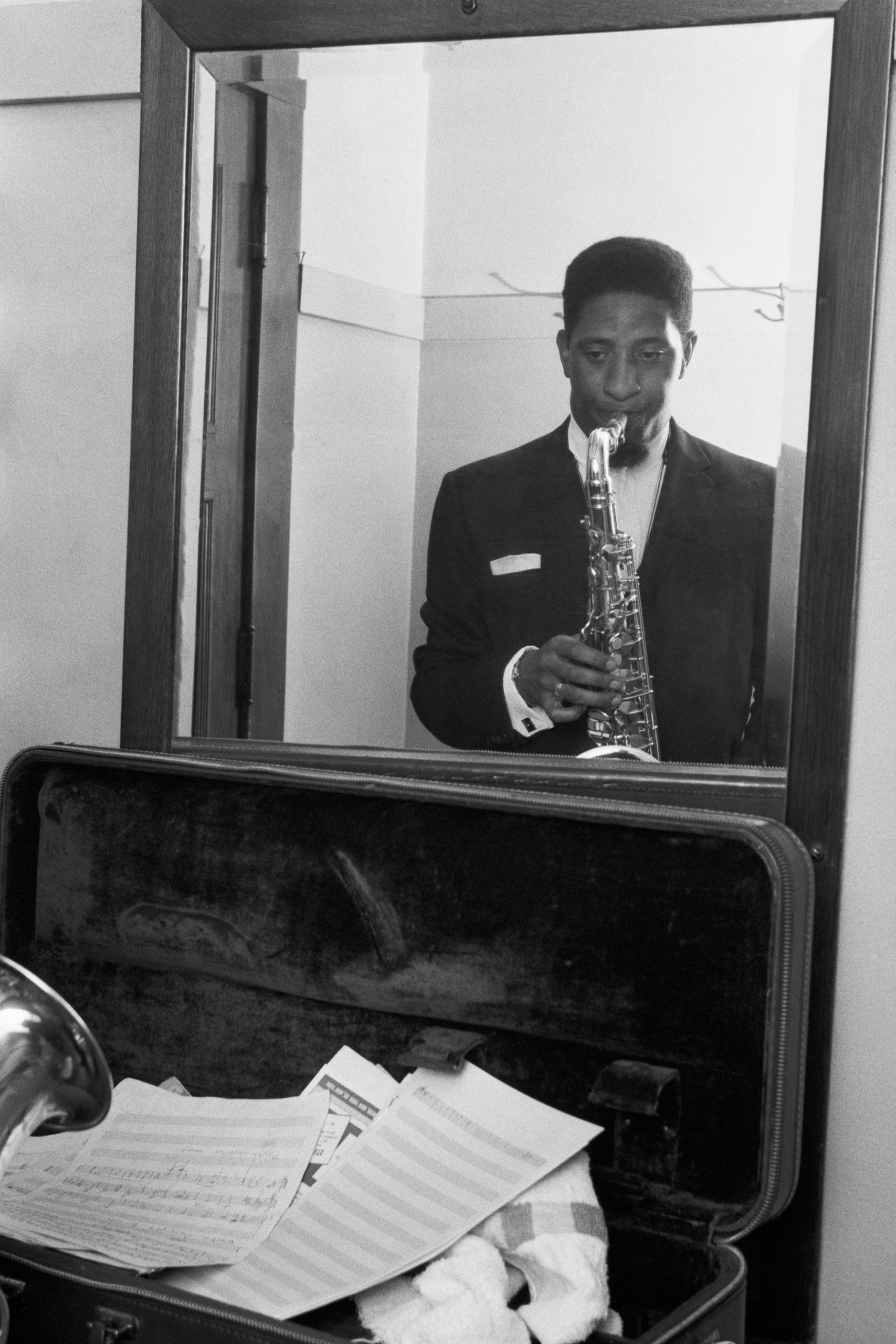 Portrait of American jazz tenor saxophonist Sonny Rollins rehearsing in front of a mirror before a concert at the Civic Opera House, Chicago, US, 1956.
