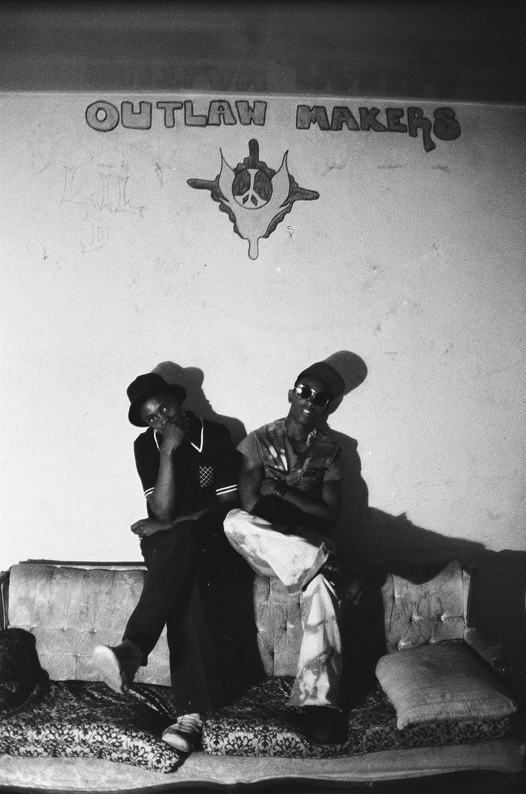 Two members of Bronx street gang the Outlaw Makers as they sit on a couch in their clubhouse, 1975.