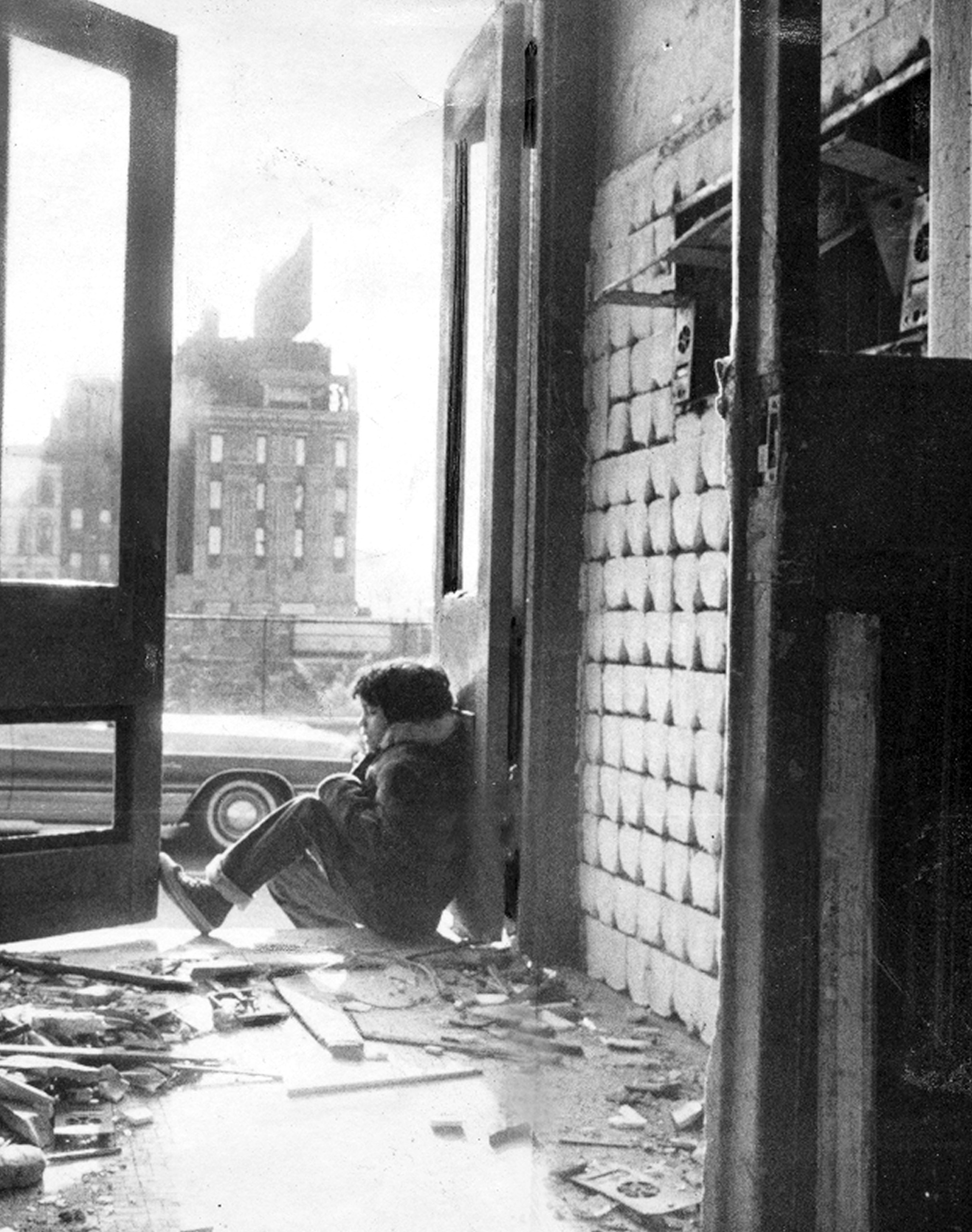 Child sits in doorway of rundown building at 135th St and Willis Ave. in the South Bronx, 1976.