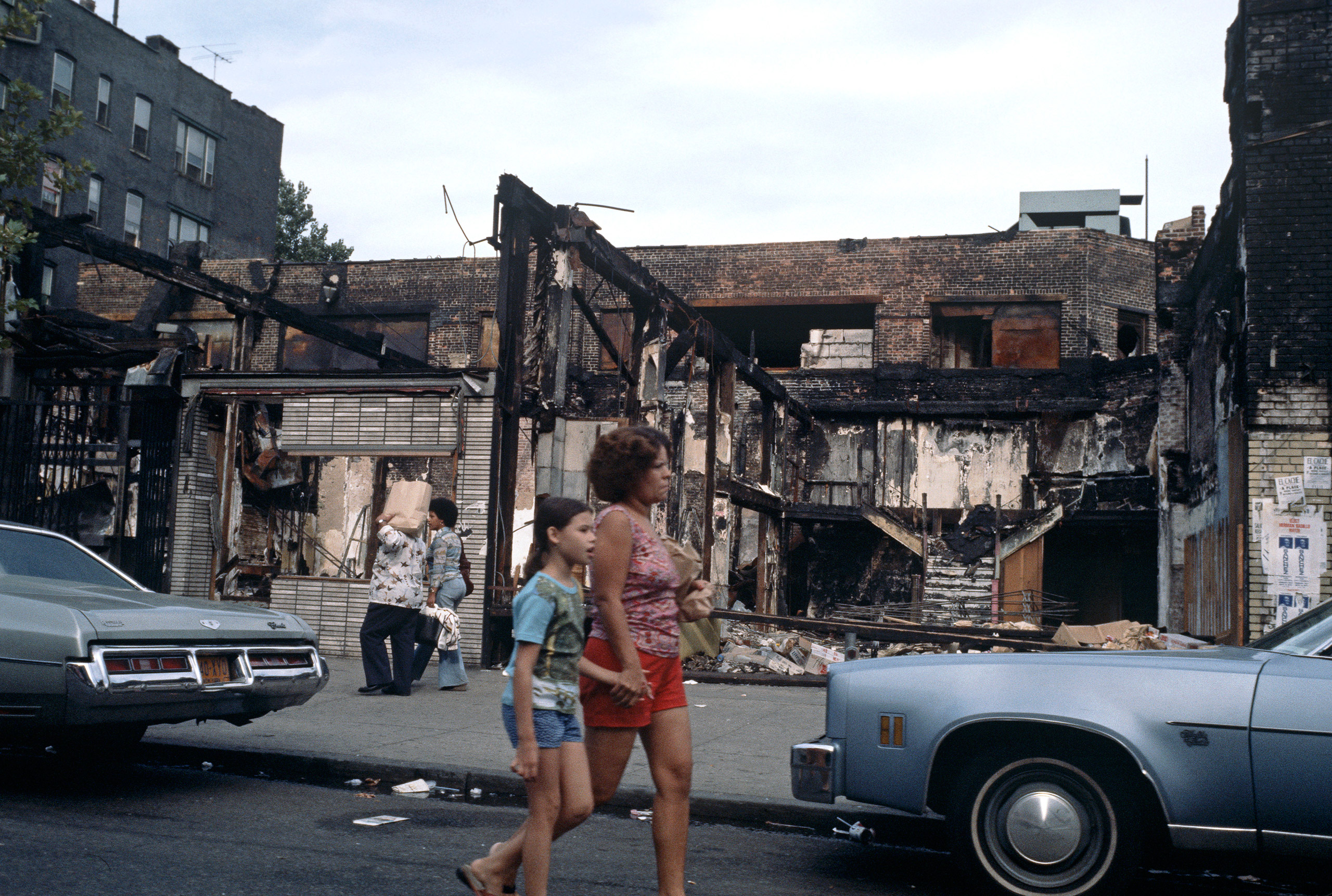 People walking by abandoned burnt-out shops in the South Bronx,1977.