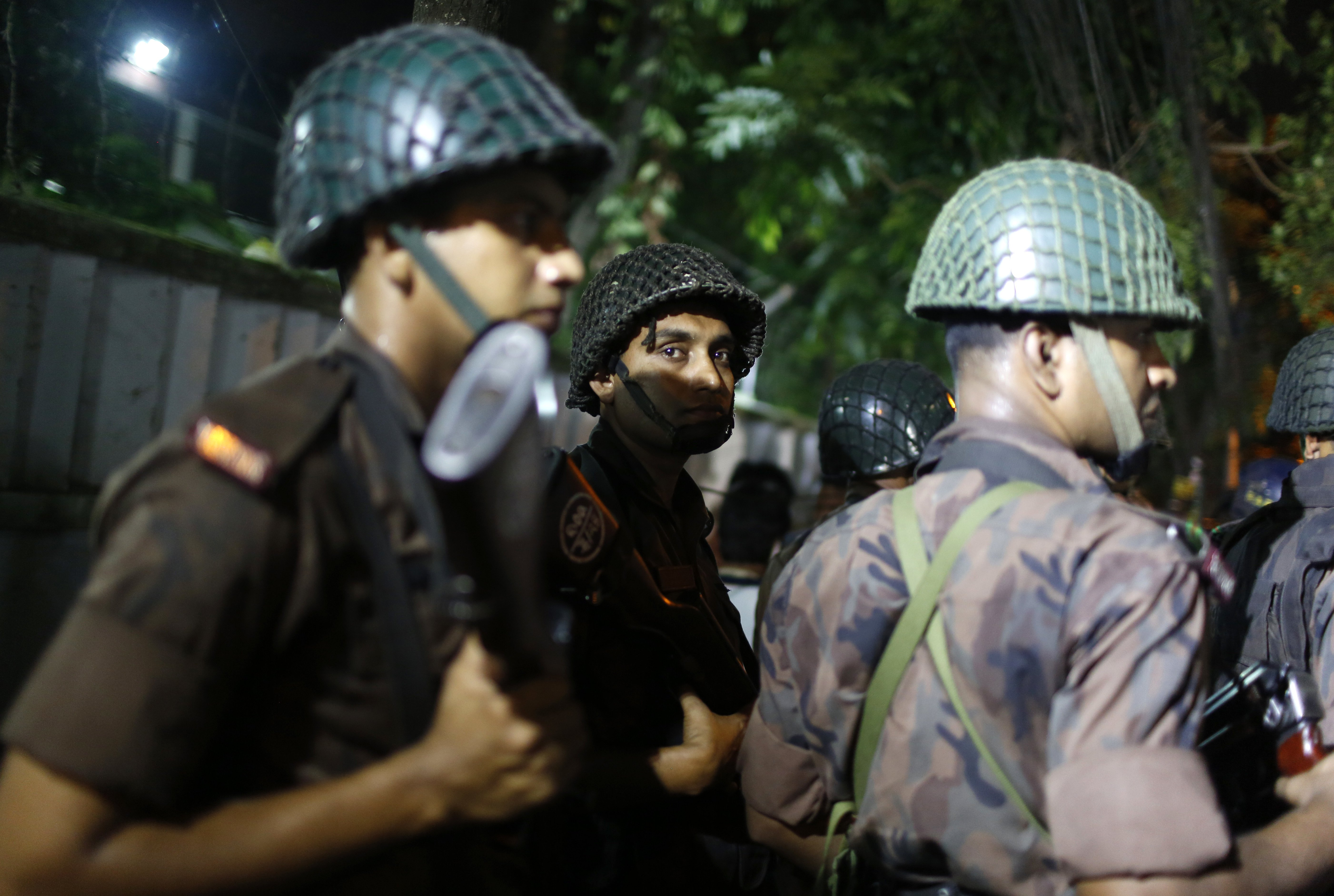Bangladeshi security personnel stand guard near a restaurant that has reportedly been attacked by unidentified gunmen in Dhaka, Bangladesh, on July 1, 2016