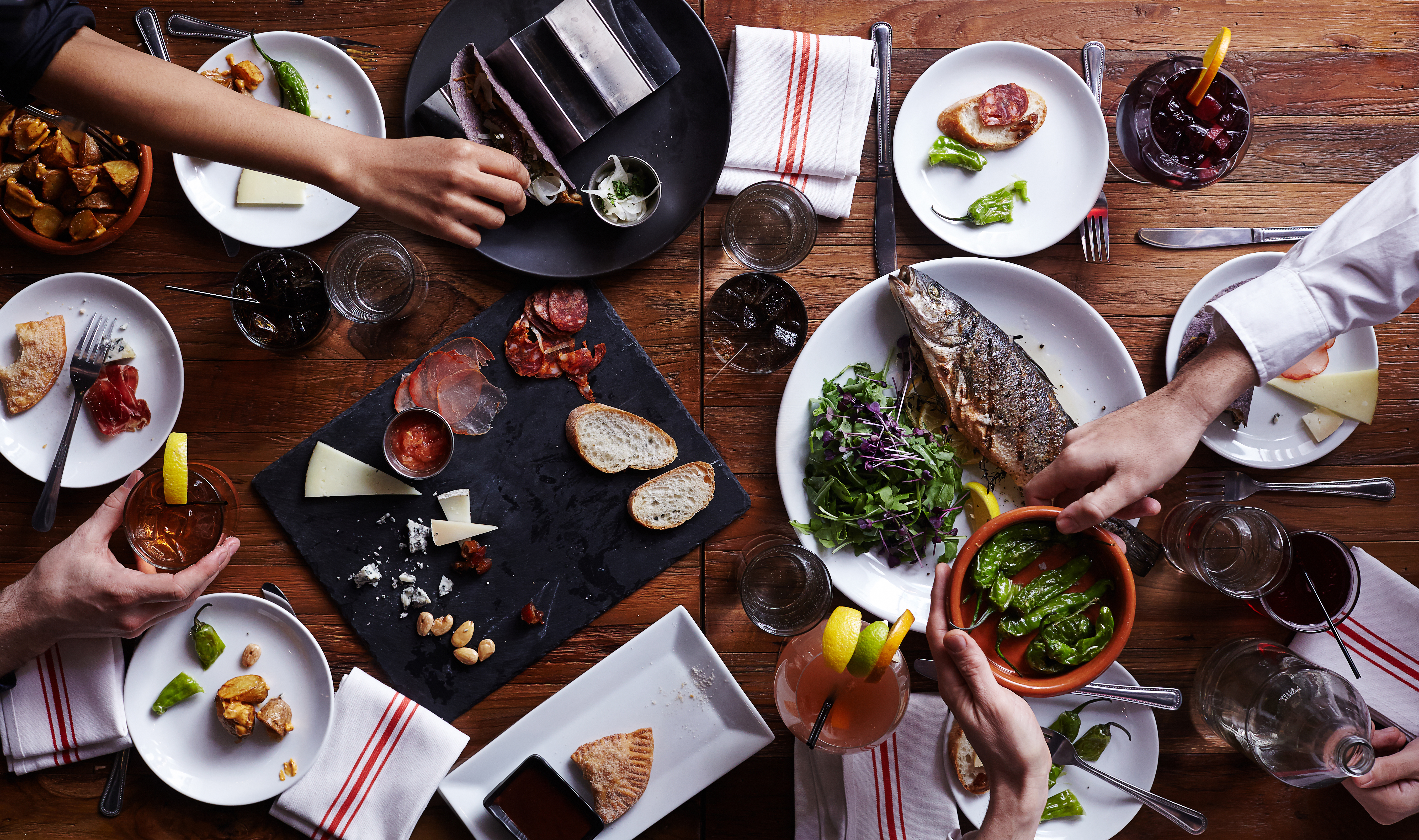 An aerial view of a group of people passing dinner plates with fish, charcuterie, and a variety of tapas and drinks.