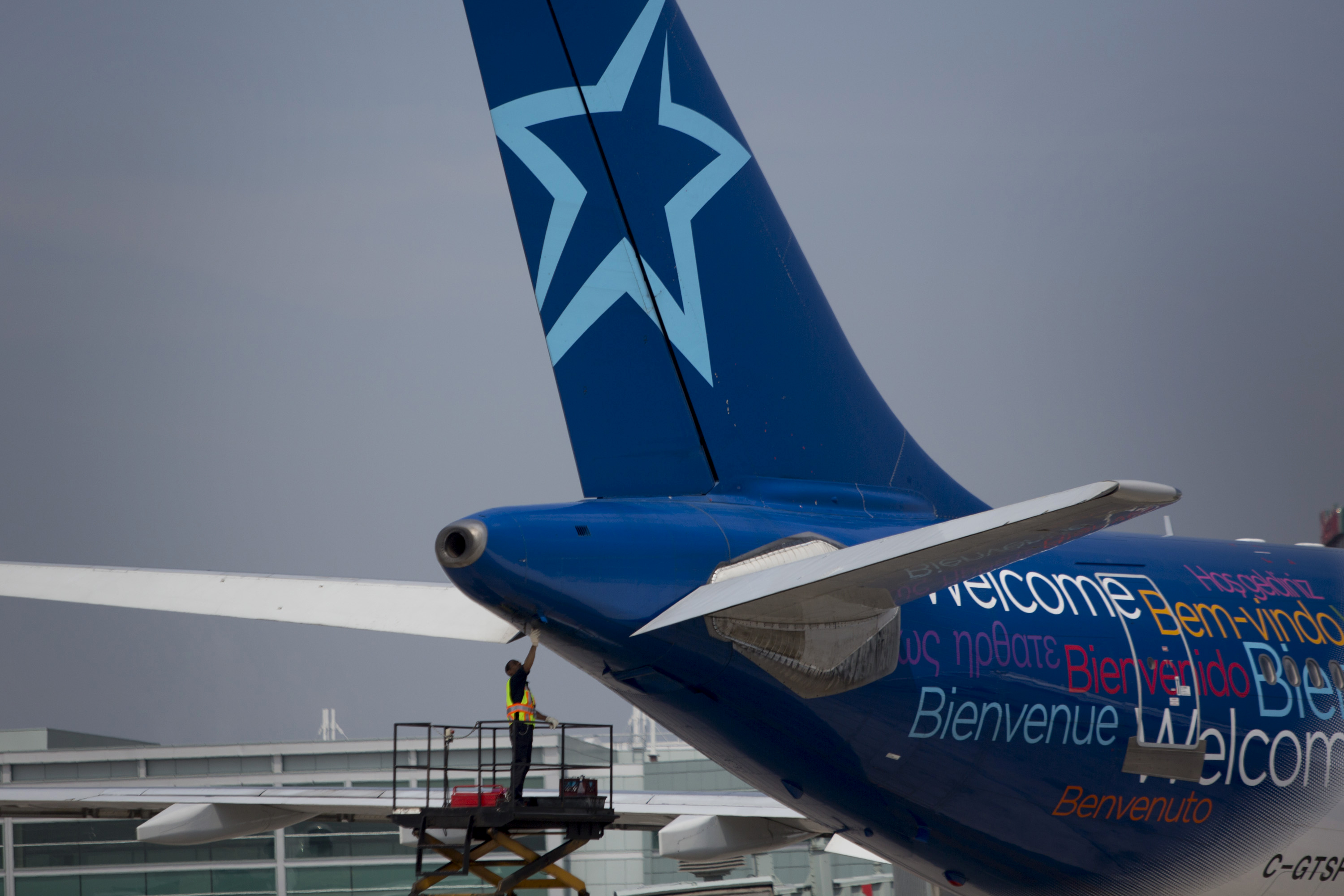 A worker inspects the rear of an Air Transat aircraft at Toronto Pearson International Airport in Toronto, Ontario, Canada, on July 3, 2013.