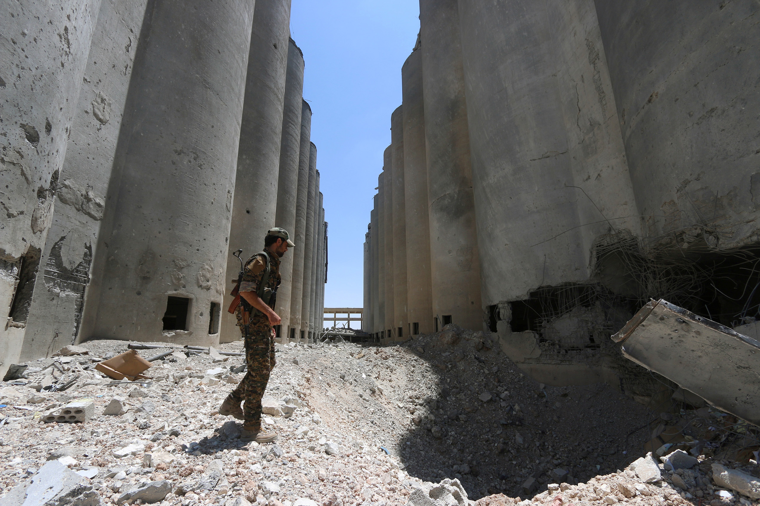 A Syria Democratic Forces (SDF) fighter walks in the silos and mills of Manbij after the SDF took control of it, in Aleppo Governorate, Syria on July 1, 2016.