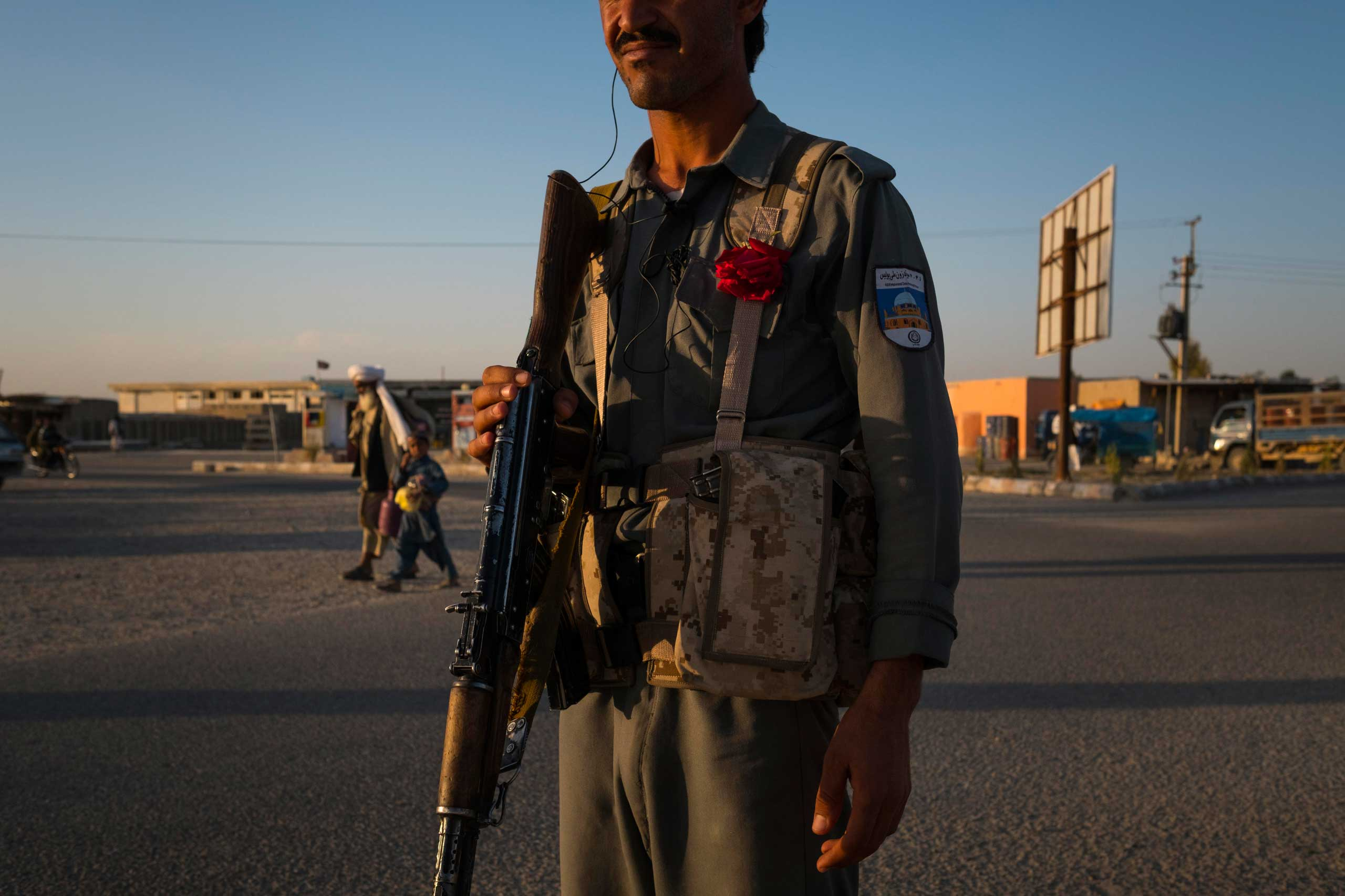 An Afghan National Policeman, wearing a red rose, at a road check point in Lashkar Gah, the capital of Helmand in southern Afghanistan. Lashkar Gah came under serious threat of being overrun in late 2015 with Taliban insurgents mounting attacks from several locations outside the city. The city remains tense with the surrounding districts contested or under the control of the Taliban and with a bloody fighting season expected still to come.