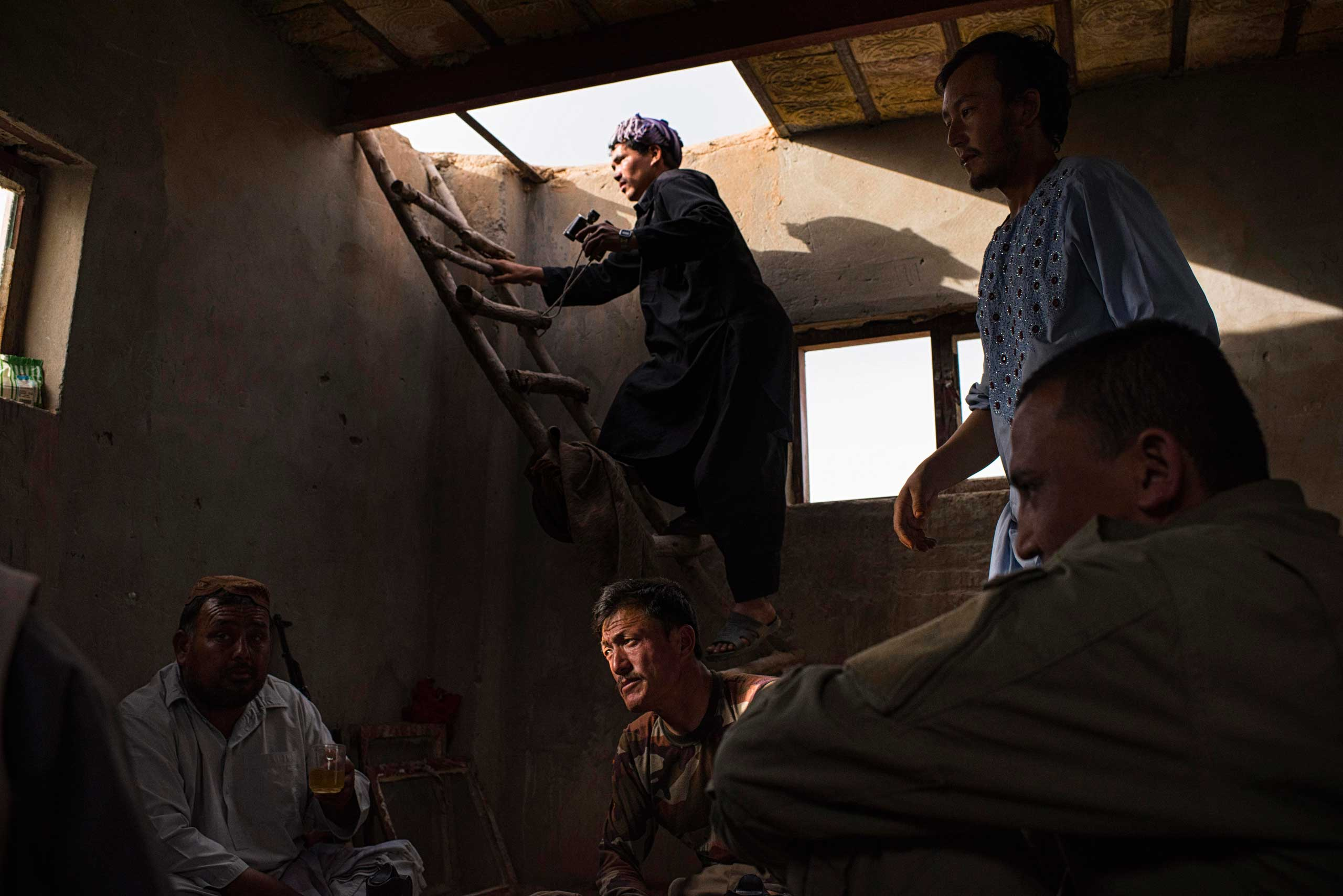 Members of the Afghan Local Police (ALP), one climbing a ladder to keep watch over adjacent fields across which Taliban have conducted raids, inside an ALP outpost in the Sayedabad area of Helmand's Nadali District. Taliban-controlled villages are only a few hundred metres away. After years of relative calm in Nadali District, the ALP, with the support of the Afghan National Army (ANA), are now maintaining the tenuous frontline against the ever-encroaching Taliban who have pushed closer than ever to the nearby Provincial capital, Lashkar Gah, in recent months. The ALP are between a rock and a hard place - unable to lay down their arms because of the immediate proximity of Taliban fighters but under-equipped to provide adequate protection for the villages they protect and call home.