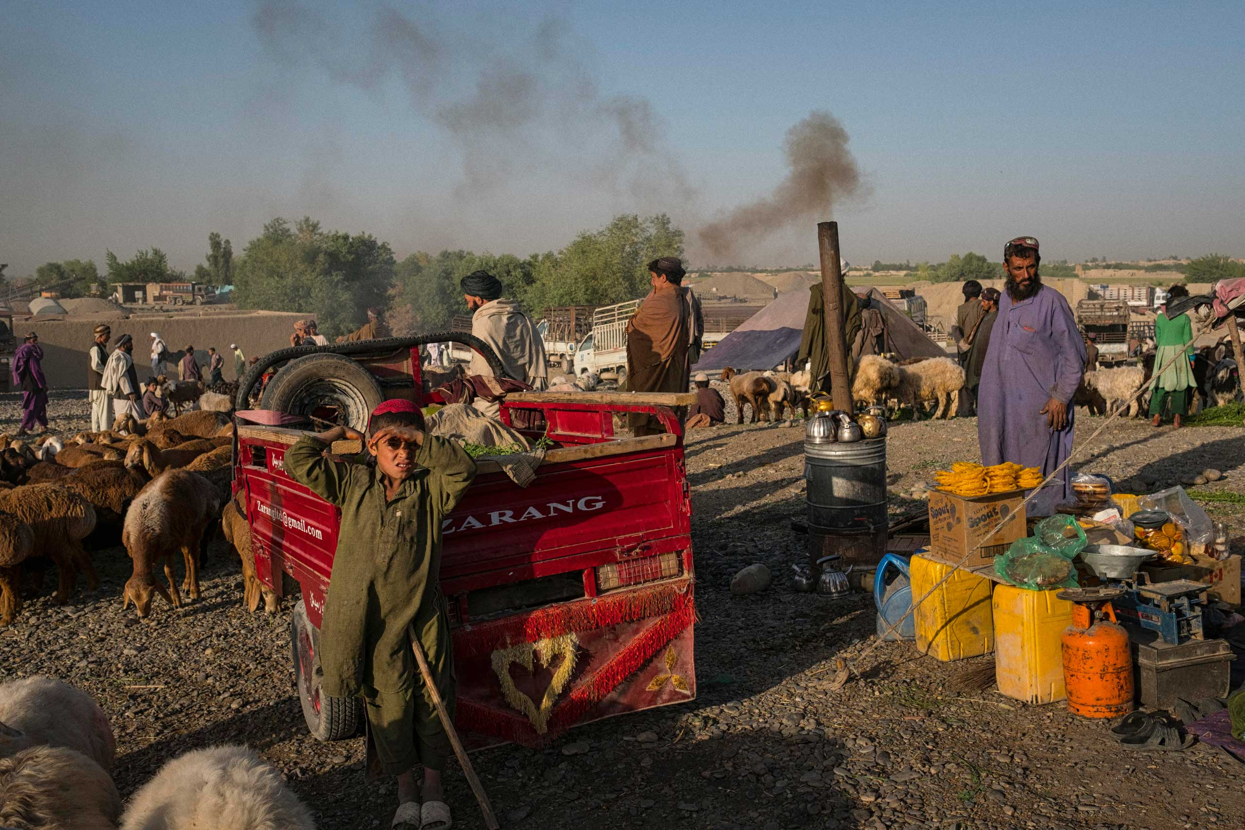 A young sheep herder and a man selling tea from a  samovar  at a regular Friday livestock bazaar in Lashkar Gah. Despite fears over deteriorating security following the Taliban's near successful attempt at pushing into the Helmand capital late in 2015, the weekly livestock bazaar attracts thousands of buyers and sellers from near and far.