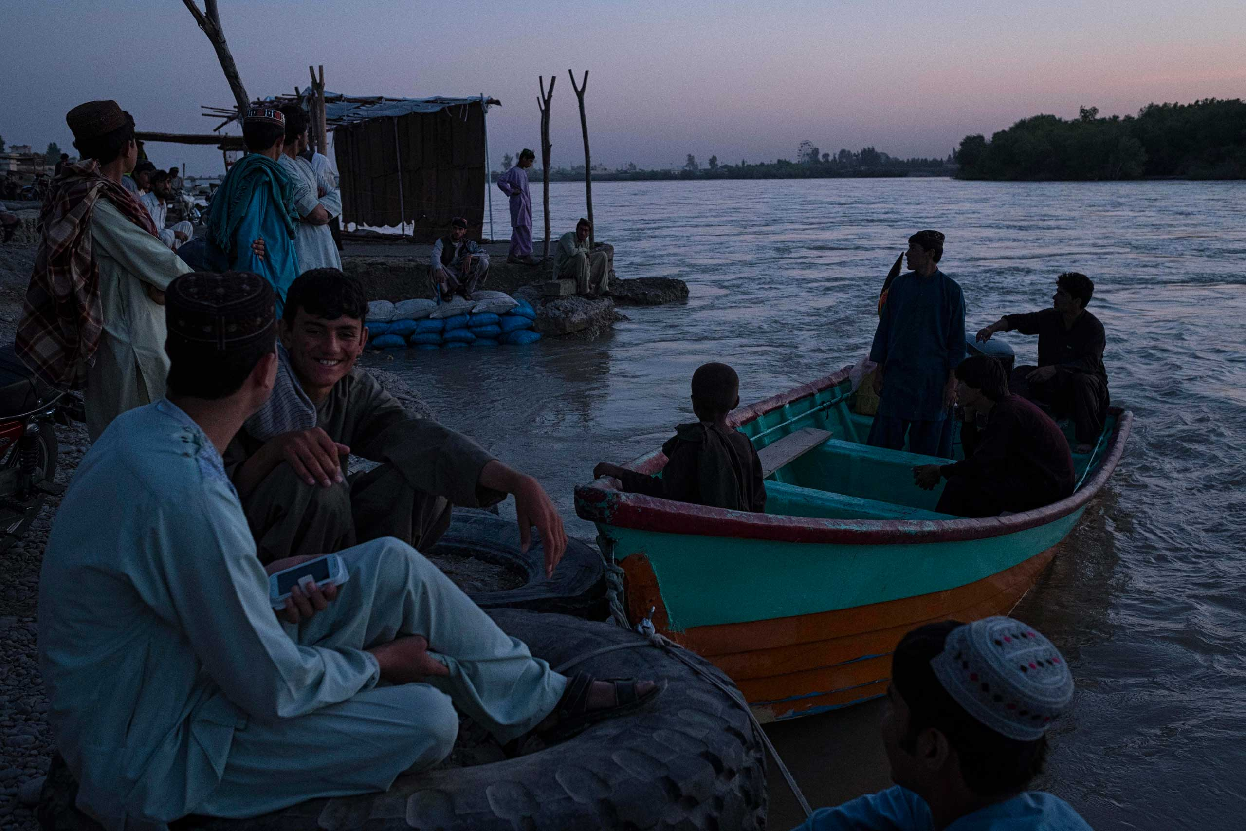 Boys and young men take in the last of the day by the Helmand River in Lashkar Gah, the capital of Helmand Province in southern Afghanistan. Lashkar Gah came under serious threat of being overrun in late 2015 with Taliban insurgents mounting attacks from several locations outside the city. The city remains tense with the surrounding districts contested or under the control of the Taliban and with a bloody fighting season expected still to come.