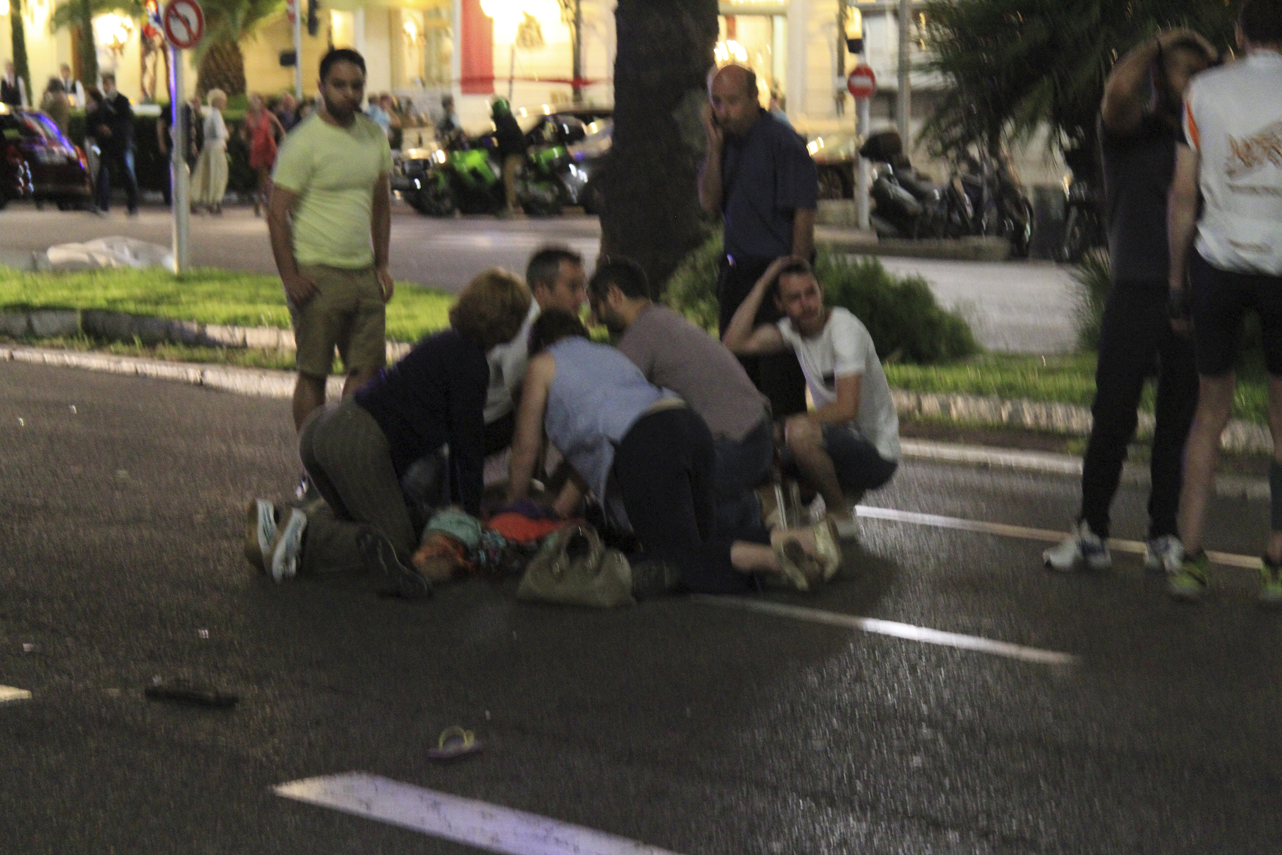 Bystanders tend to victims after a terrorist attack in Nice, France, that  left 77 dead and many more injured, July 14, 2016