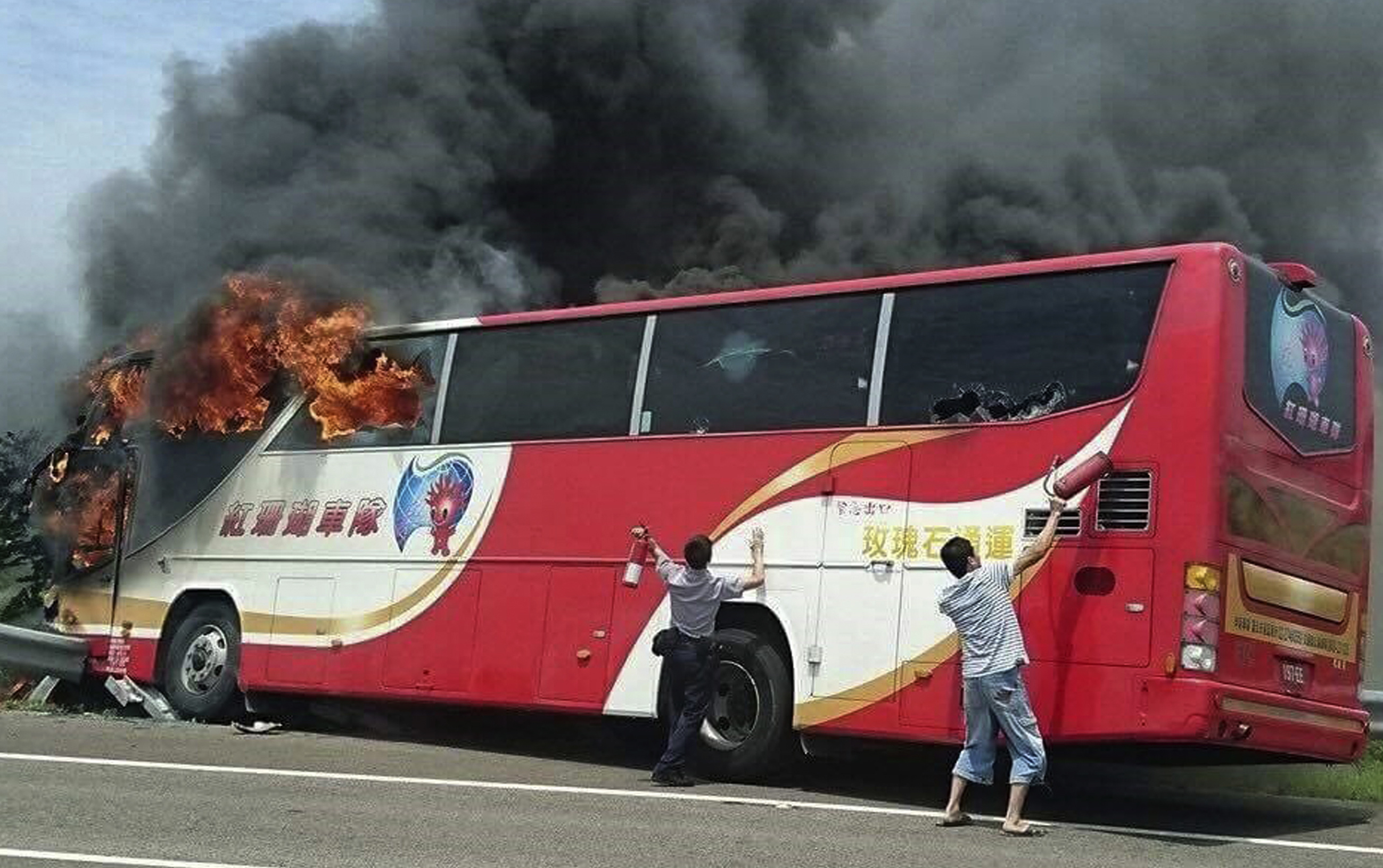 In this photo provided by Yan Cheng, a policeman and another man try to break the windows of a burning tour bus on the side of a highway in Taoyuan, Taiwan,  July 19, 2016