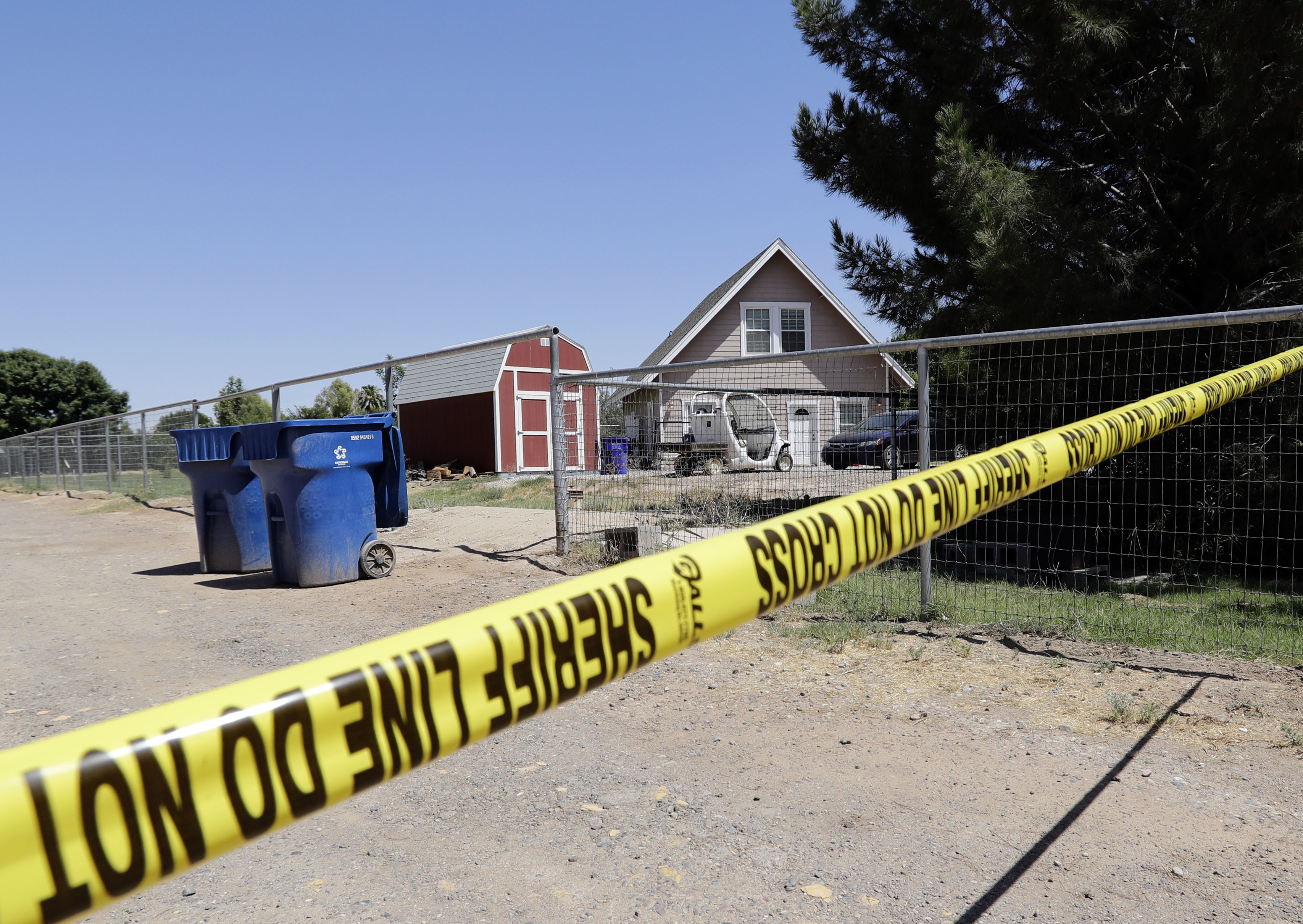Crime scene tape blocks the entrance to a home where multiple bodies were found, Tuesday, July 26, 2016, in Gilbert, Ariz. Ω