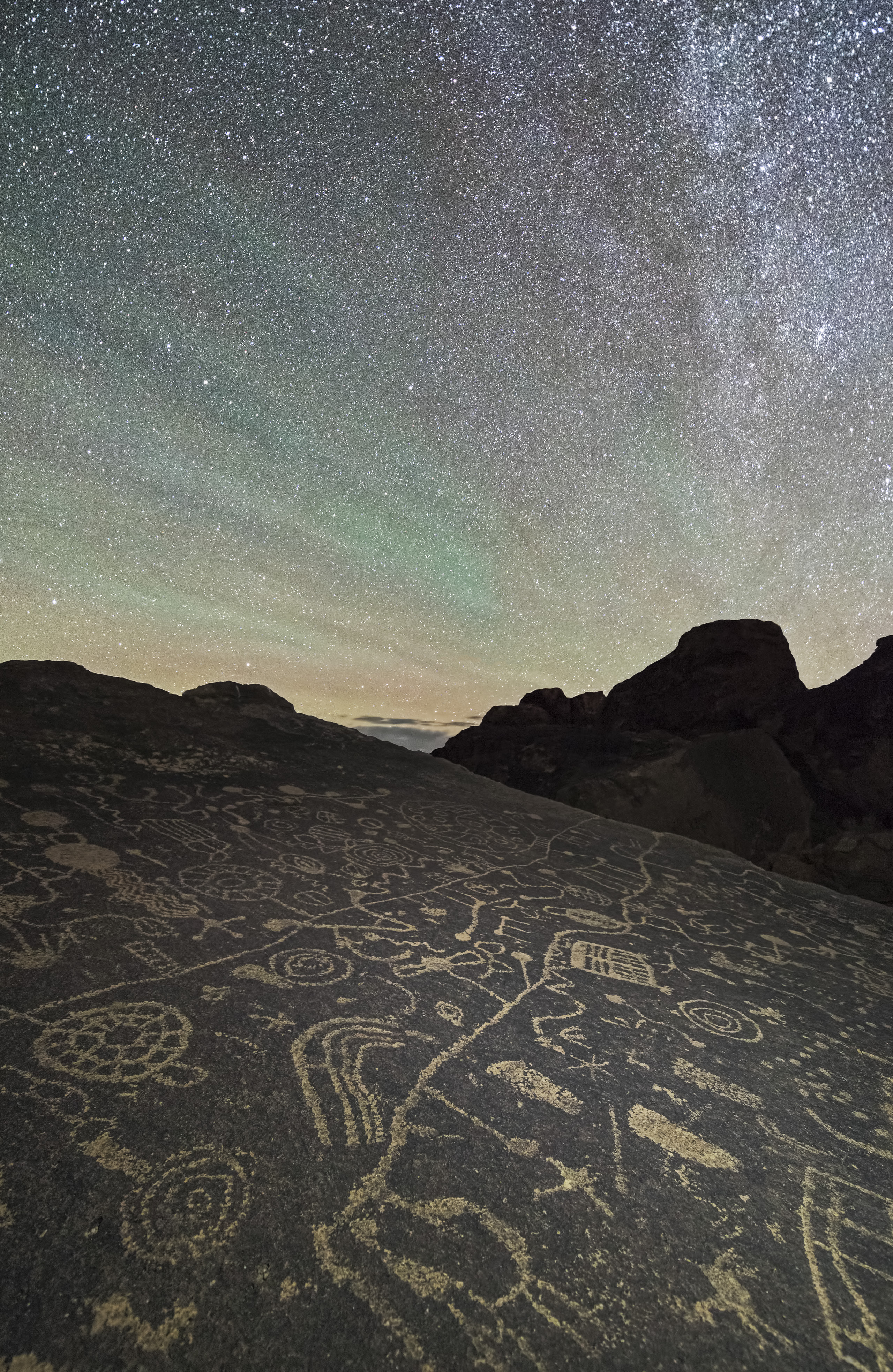 Ancient petroglyphs are lit up by the glittering stars of the night sky in the Eastern Sierras in Calif.