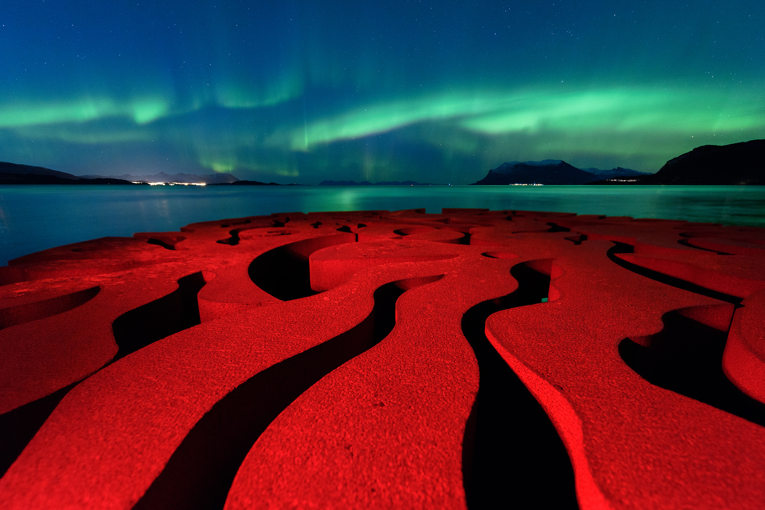 The rusty red swirls of the circular, iron sculpture, Seven Magic Points, in Brattebergan, Norway, mirror the rippling aurora above.