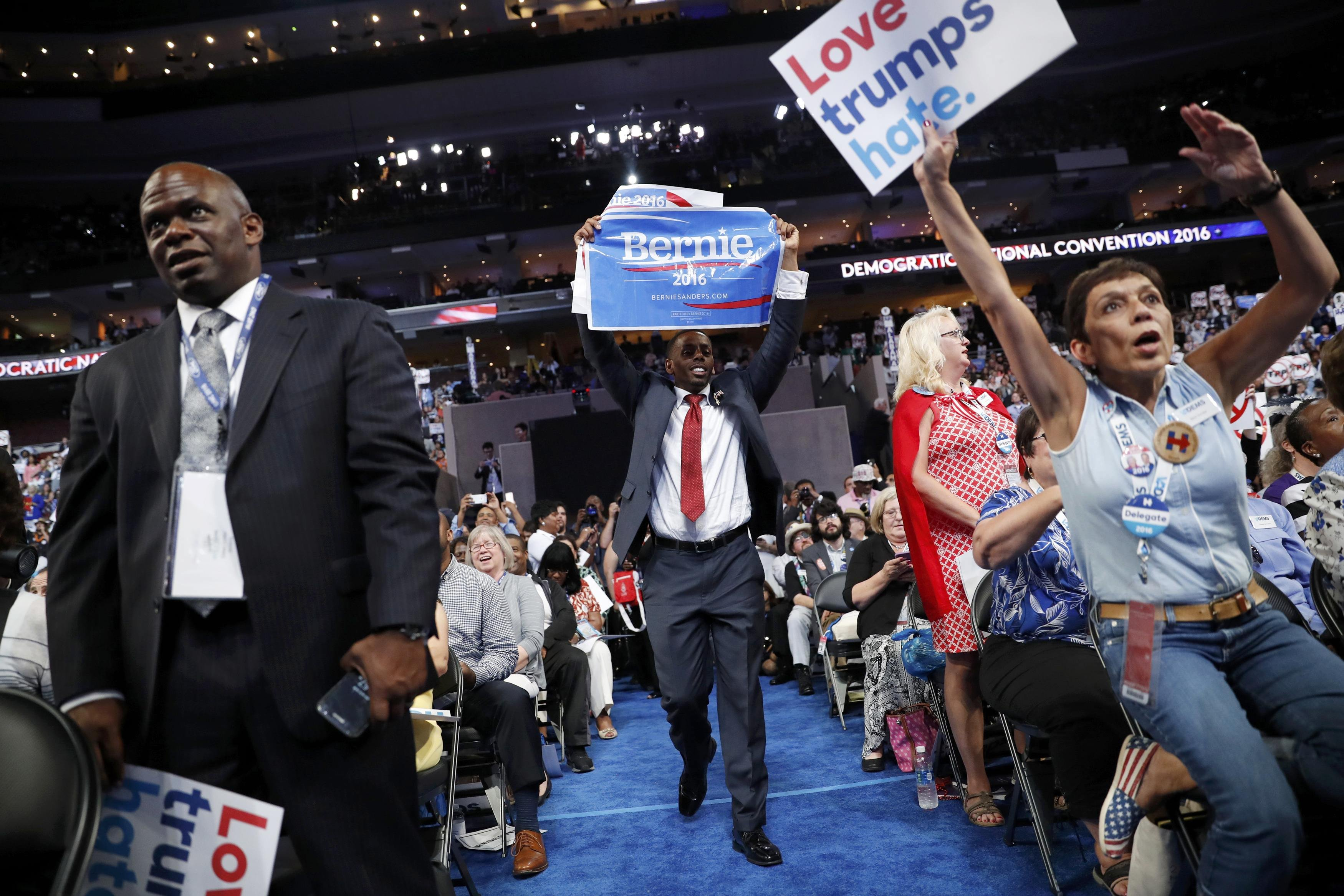 A supporter of former Democratic presidential candidate Bernie Sanders approaches the podium with a Sanders campaign sign during the report of the Rules Committee at the Democratic National Convention in Philadelphia on July 25, 2016.