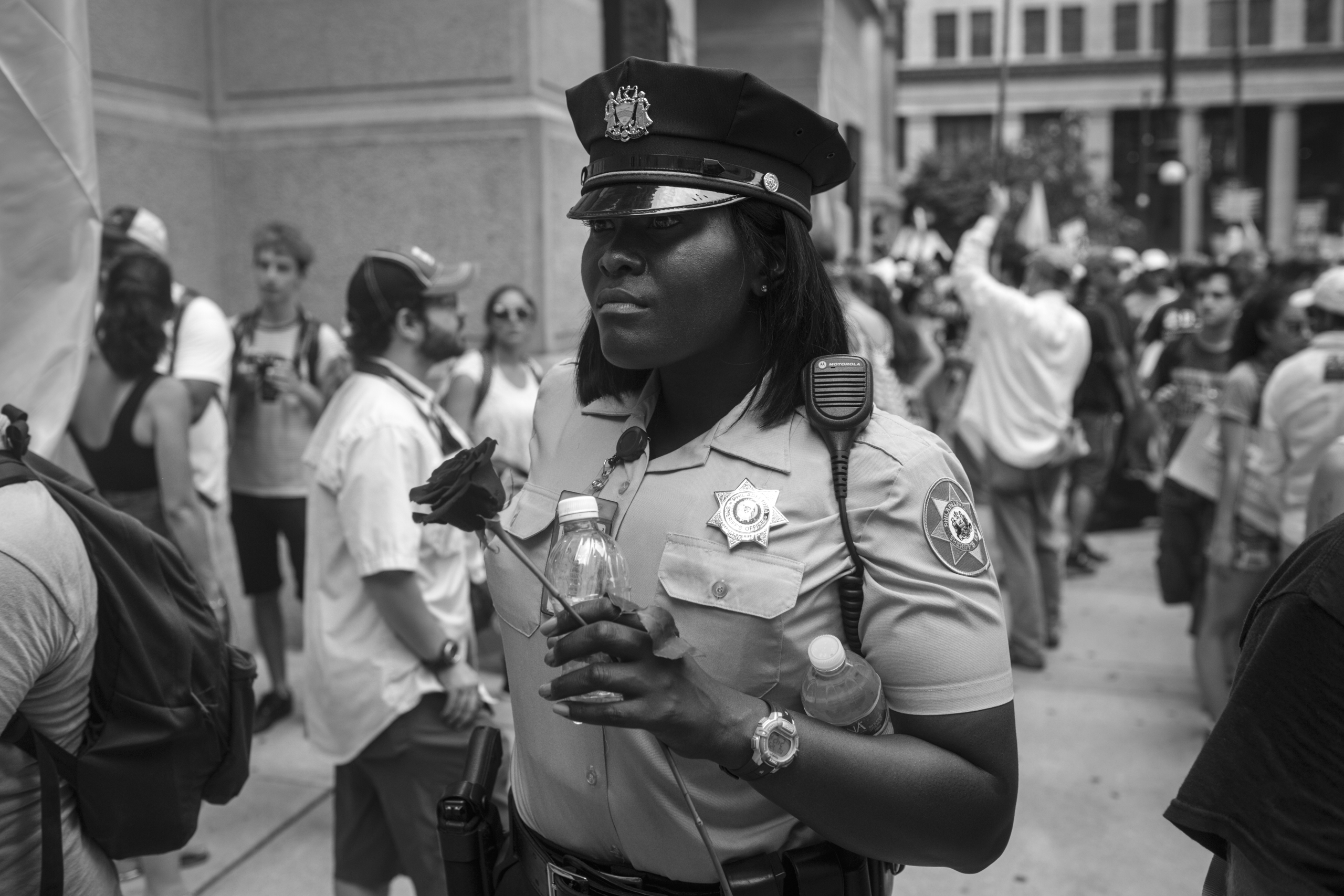 25 July 2016 - Philadelphia, PA - A police officer is holding a rose, while people gather for a rally at City Hall on the first day of the Democratic National Convention.