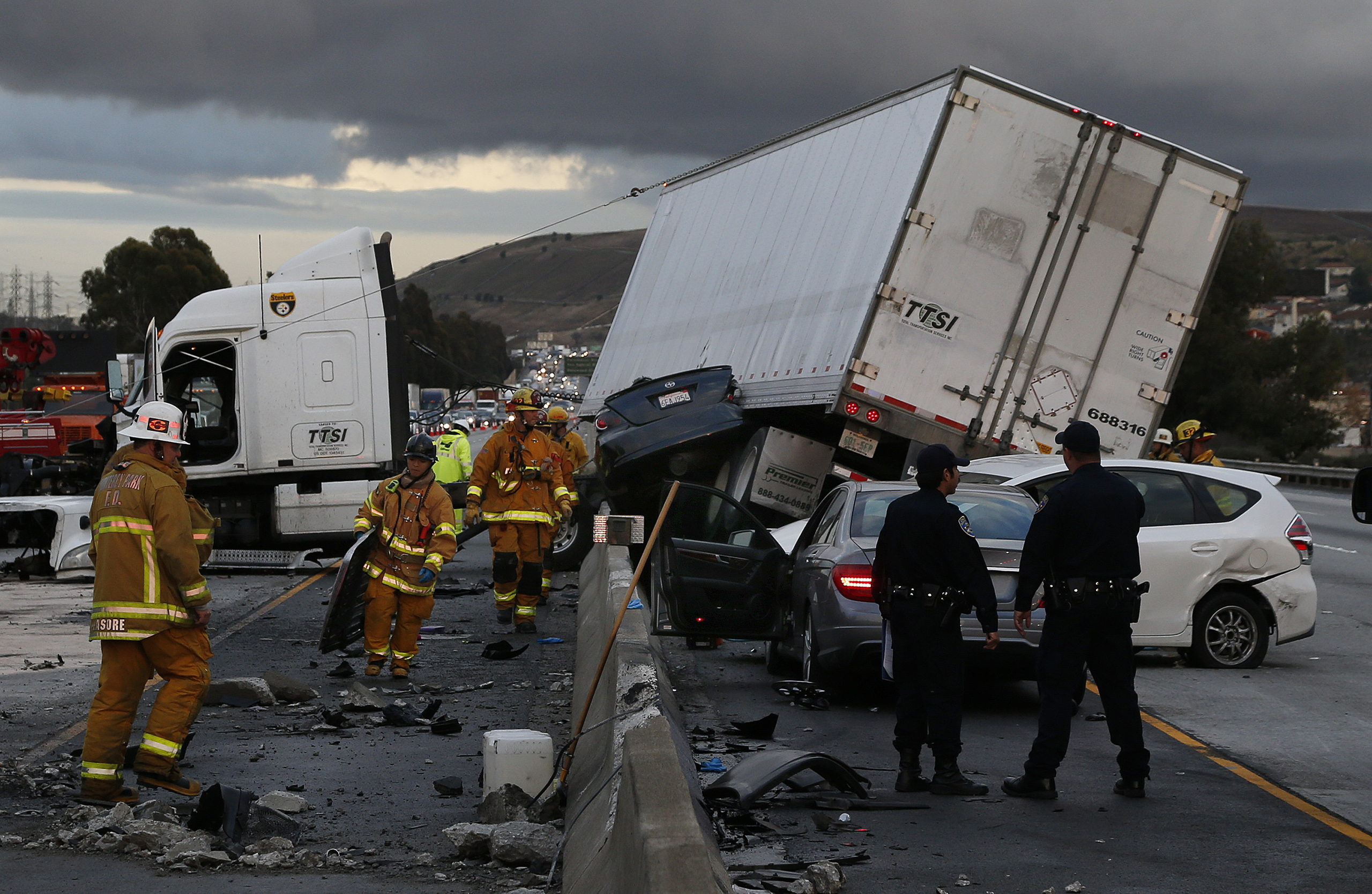 Firefighters and rescue personnel are on scene after a big rig crashed through the center divider crushing a car underneath and causing four other vehicles to collide on the rain slicked 60 freeway near the Garfield Exit in Monterey Park, Calif.  on January 5, 2016.