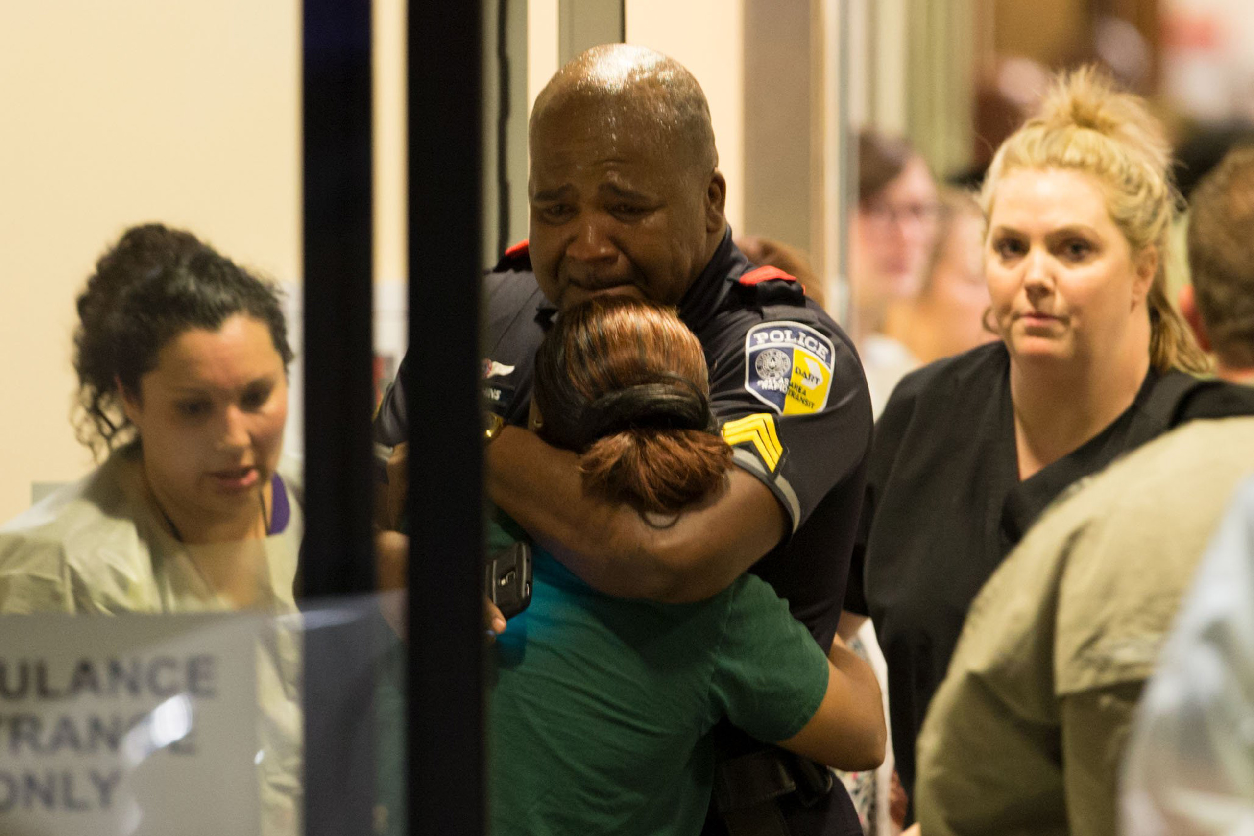 A Dallas Area Rapid Transit police officer receives comfort at the Baylor University Hospital emergency room entrance on July 7, 2016.